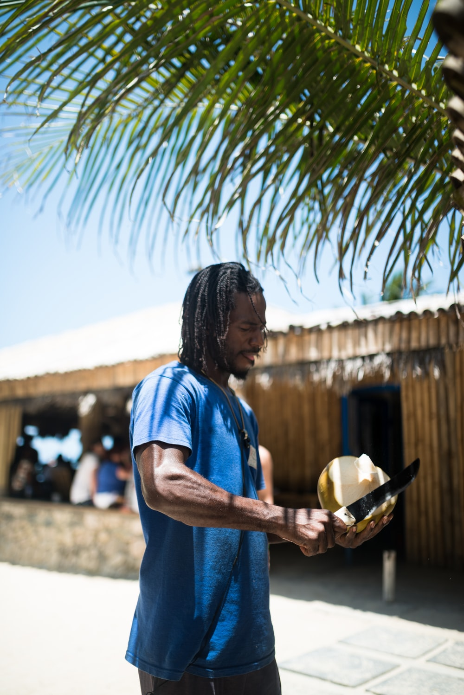 man peeling coconut