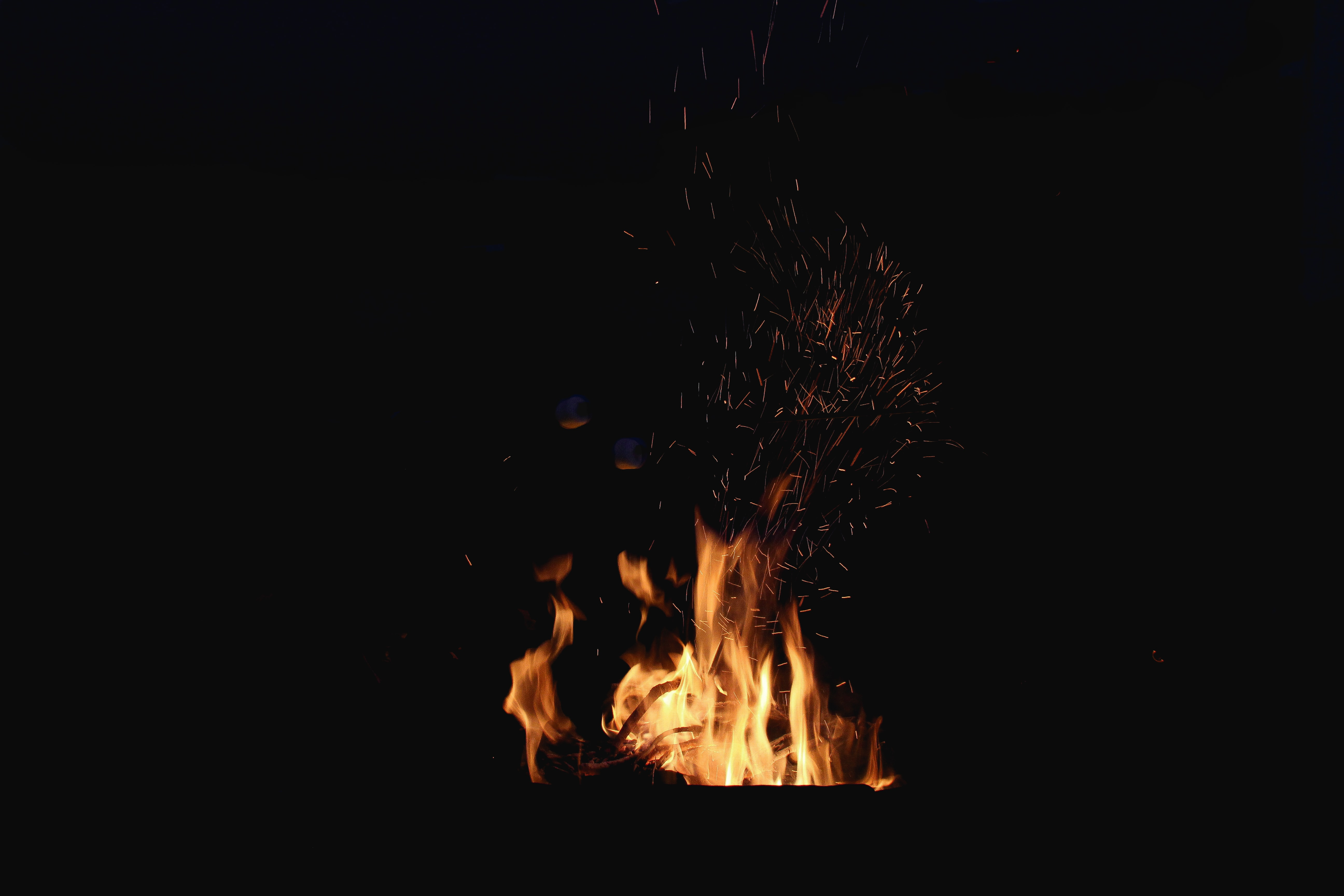 A bright orange fire with ash flying off at night at a campsite