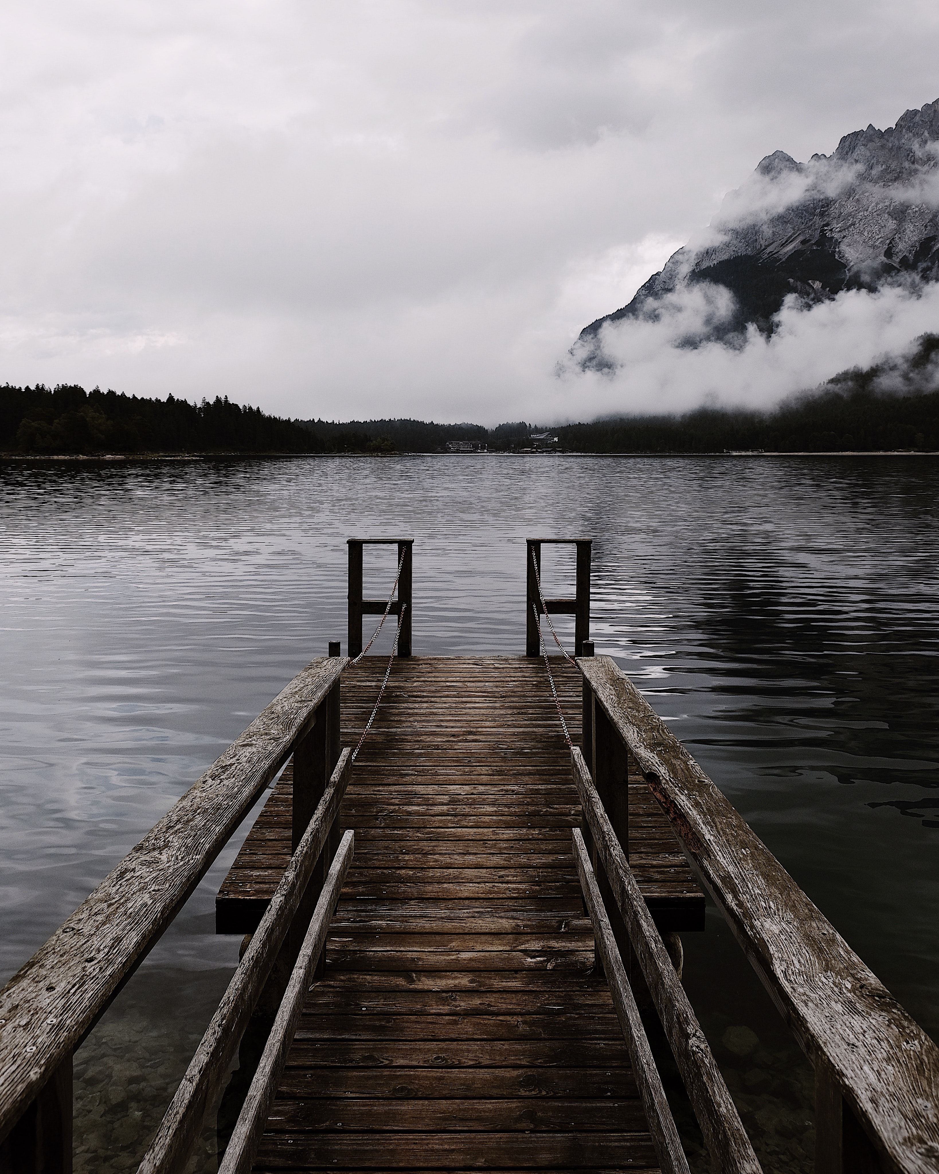 Desolate pier leads to a calm lake with mountain views