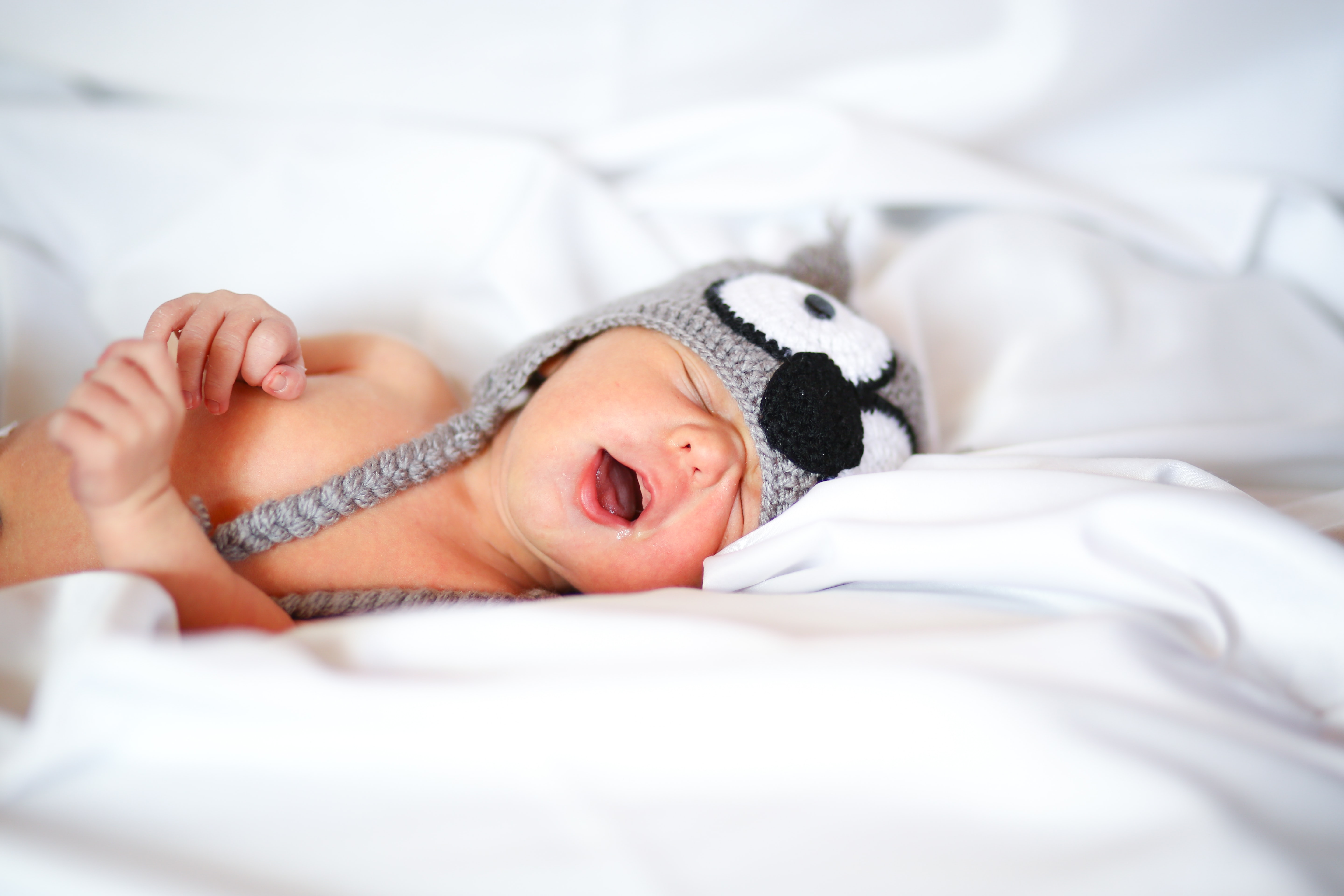 baby lying on bed with mouth open