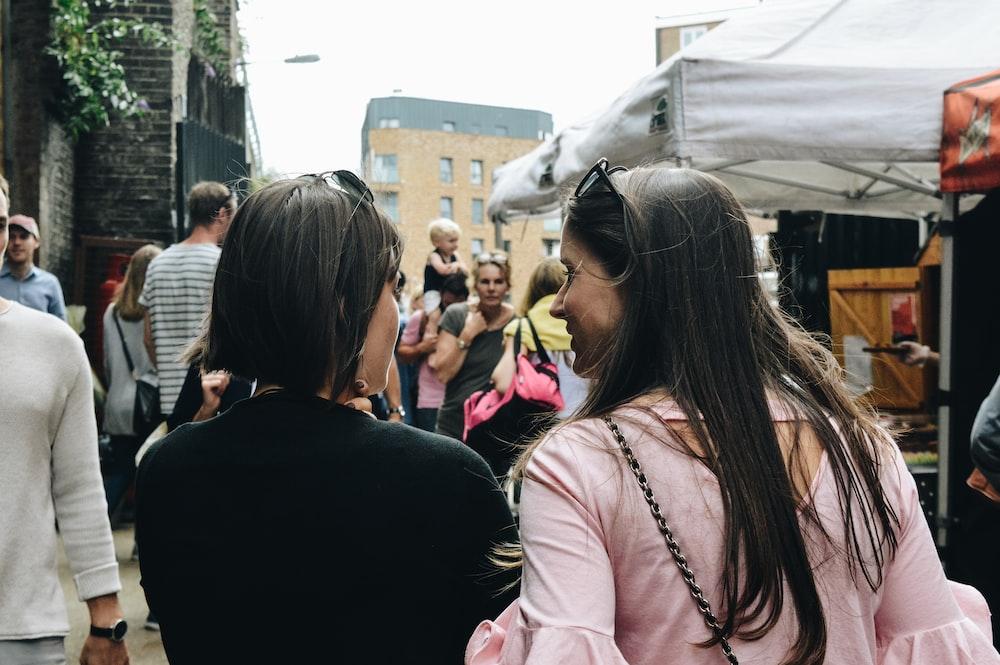 two women walking near food stalls