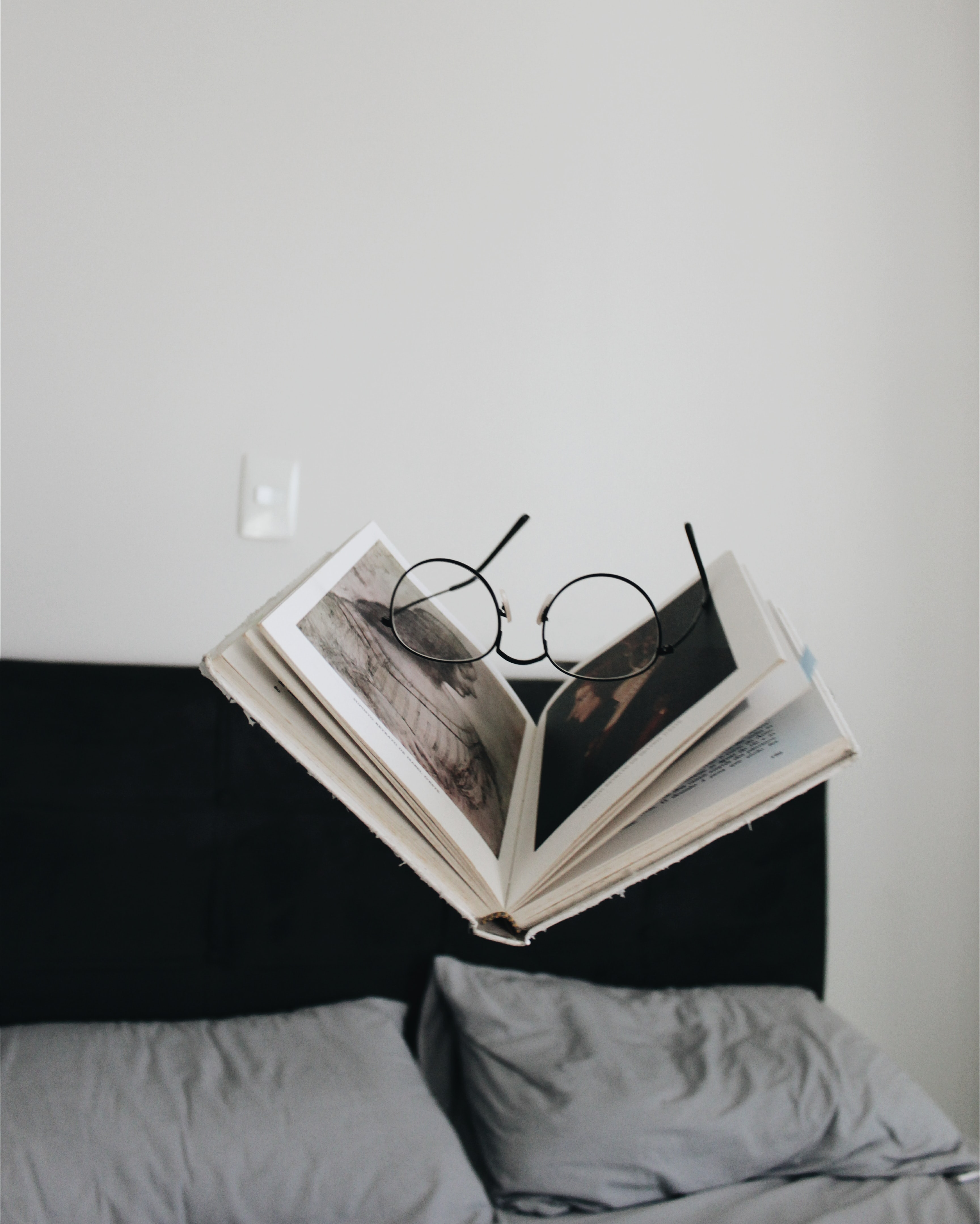 A pair of glasses on a half-open book floating above a double bed