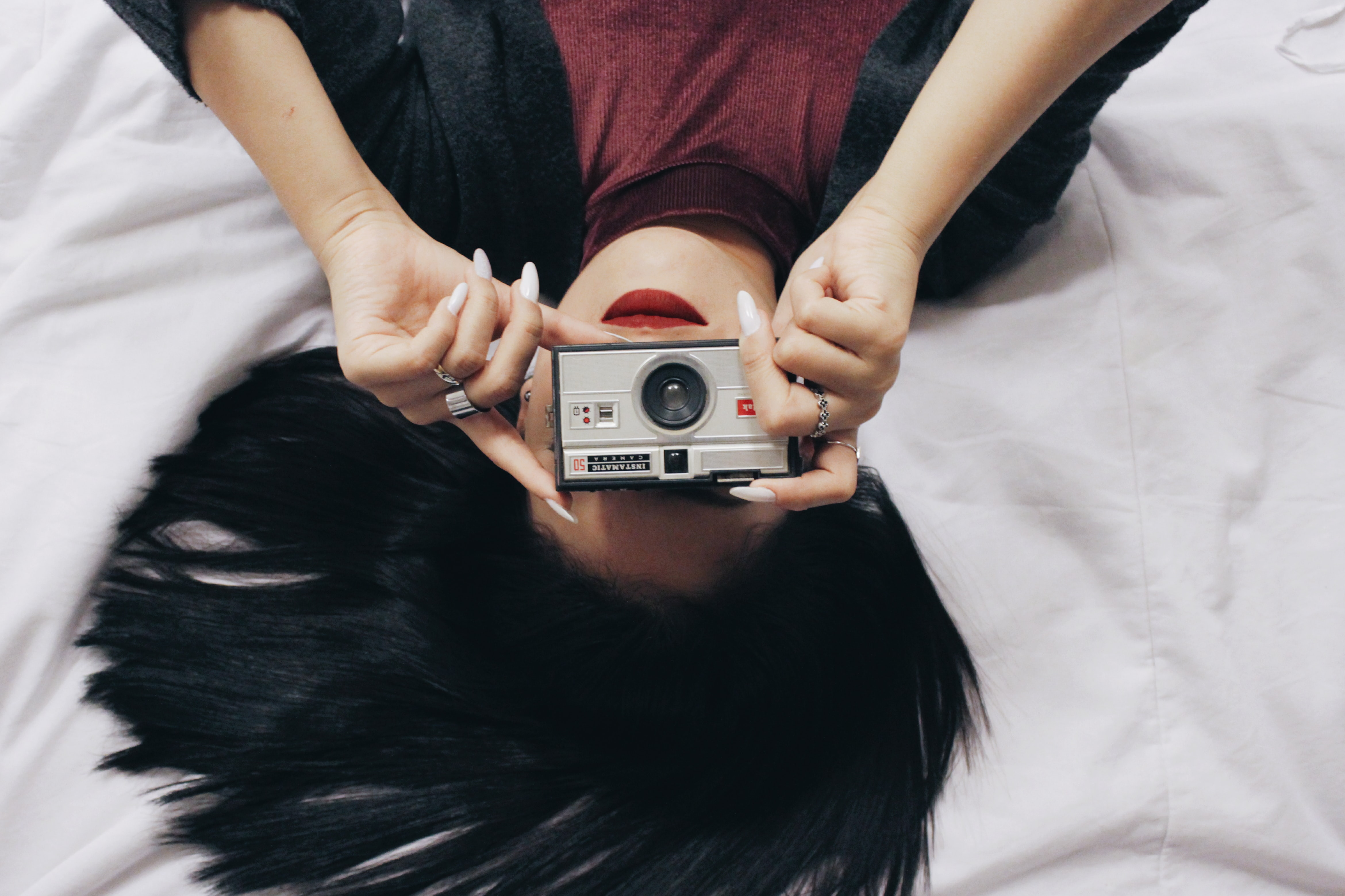 A woman in red lipstick with black hair lying on her back, taking a photo