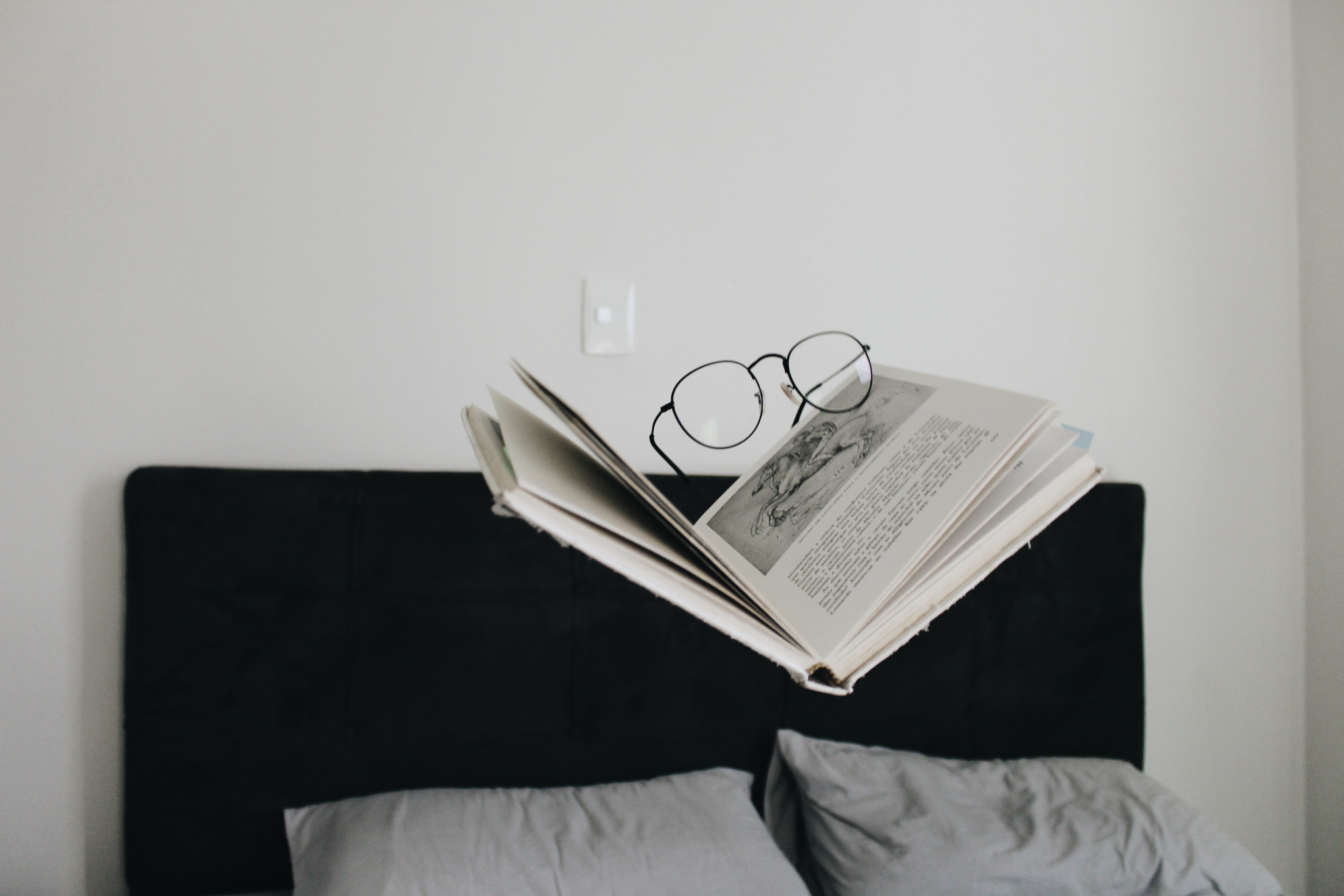 eyeglasses on top of book above bed