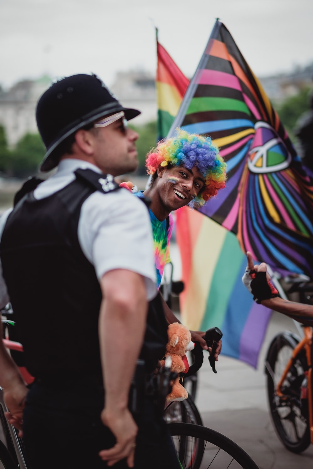 person wearing rainbow wig riding bicycle