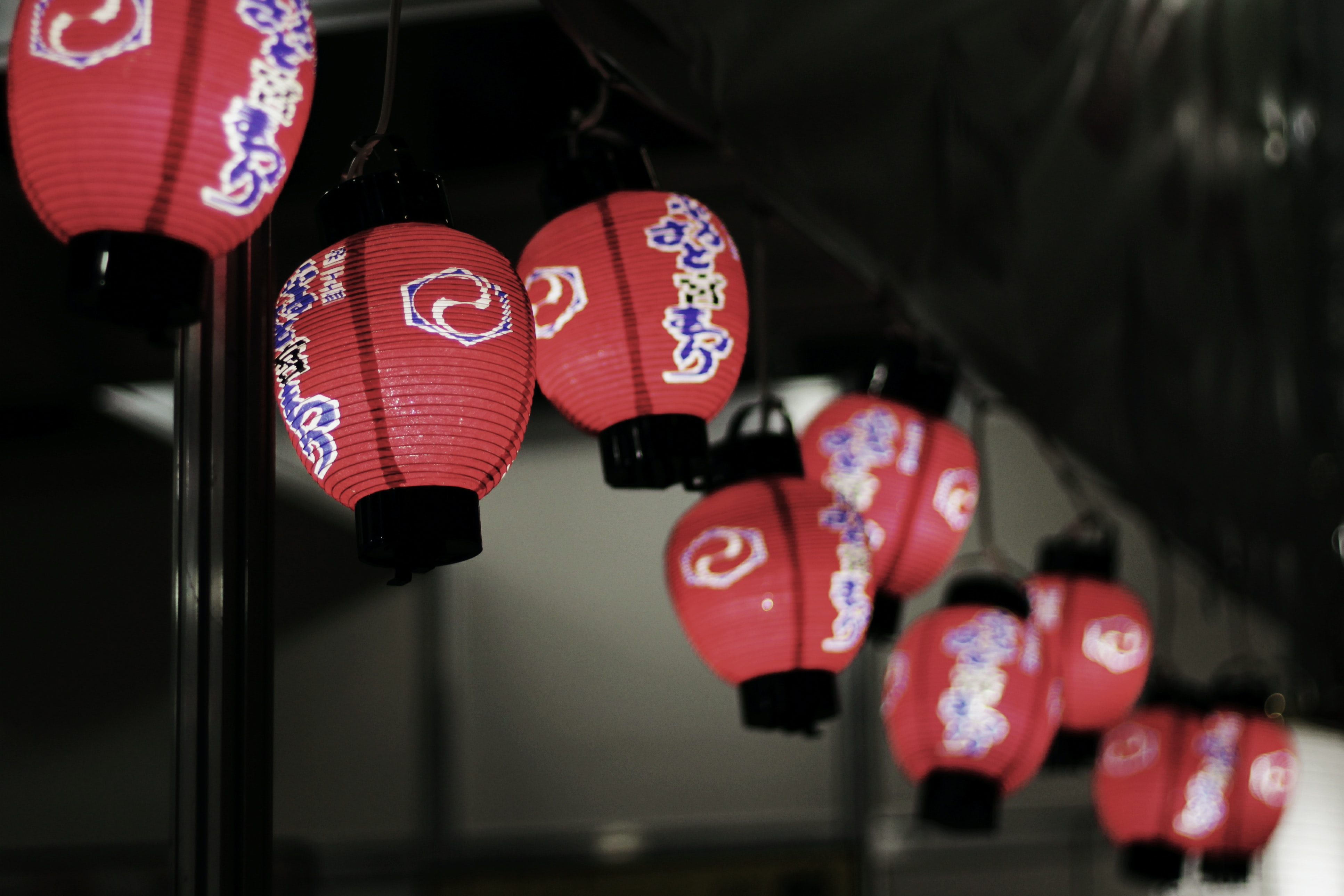 Red japanese lanterns hanging from the ceiling indoors