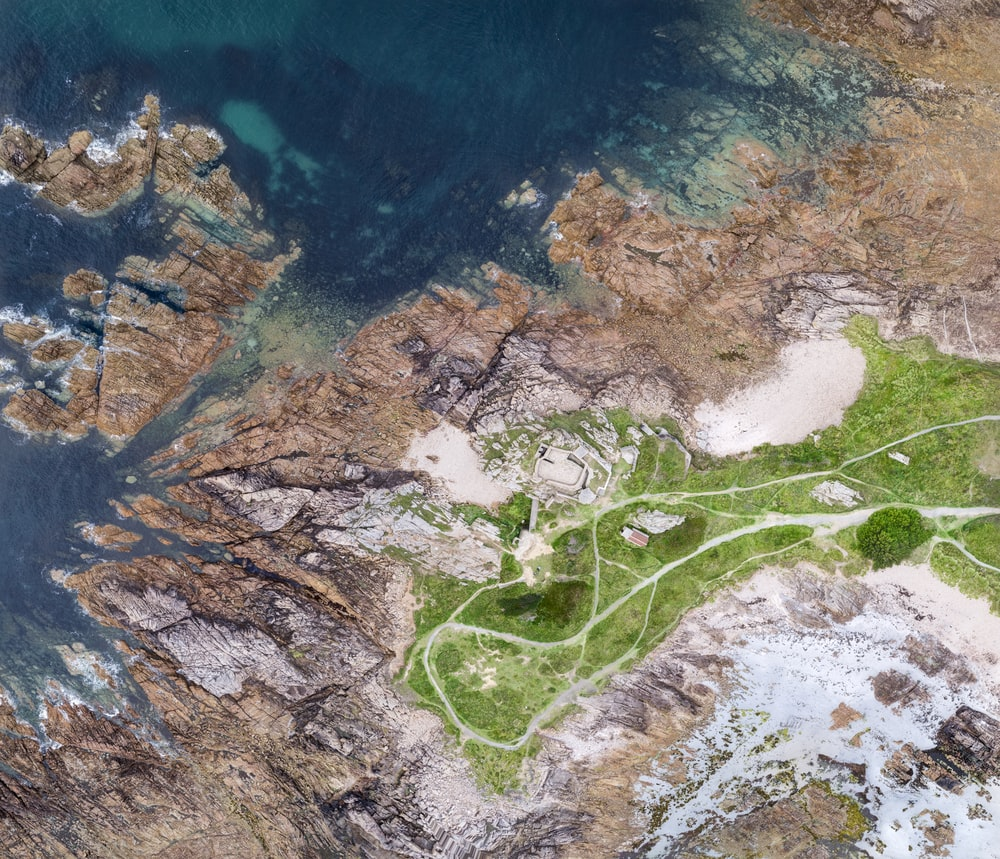 aerial view of green grass near body of water during daytime