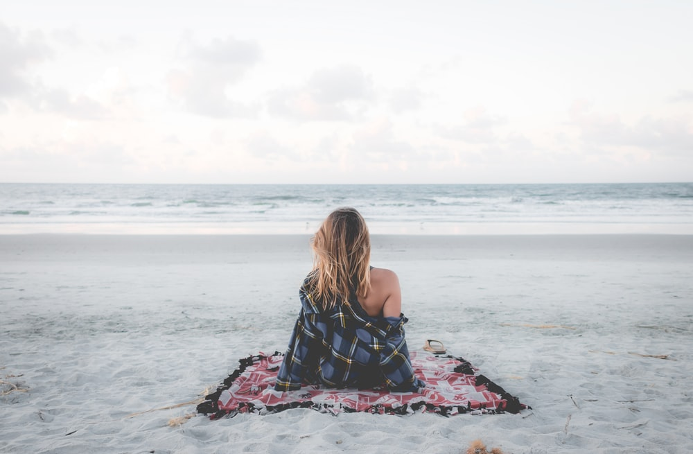 woman sitting on blanket located on shoreline