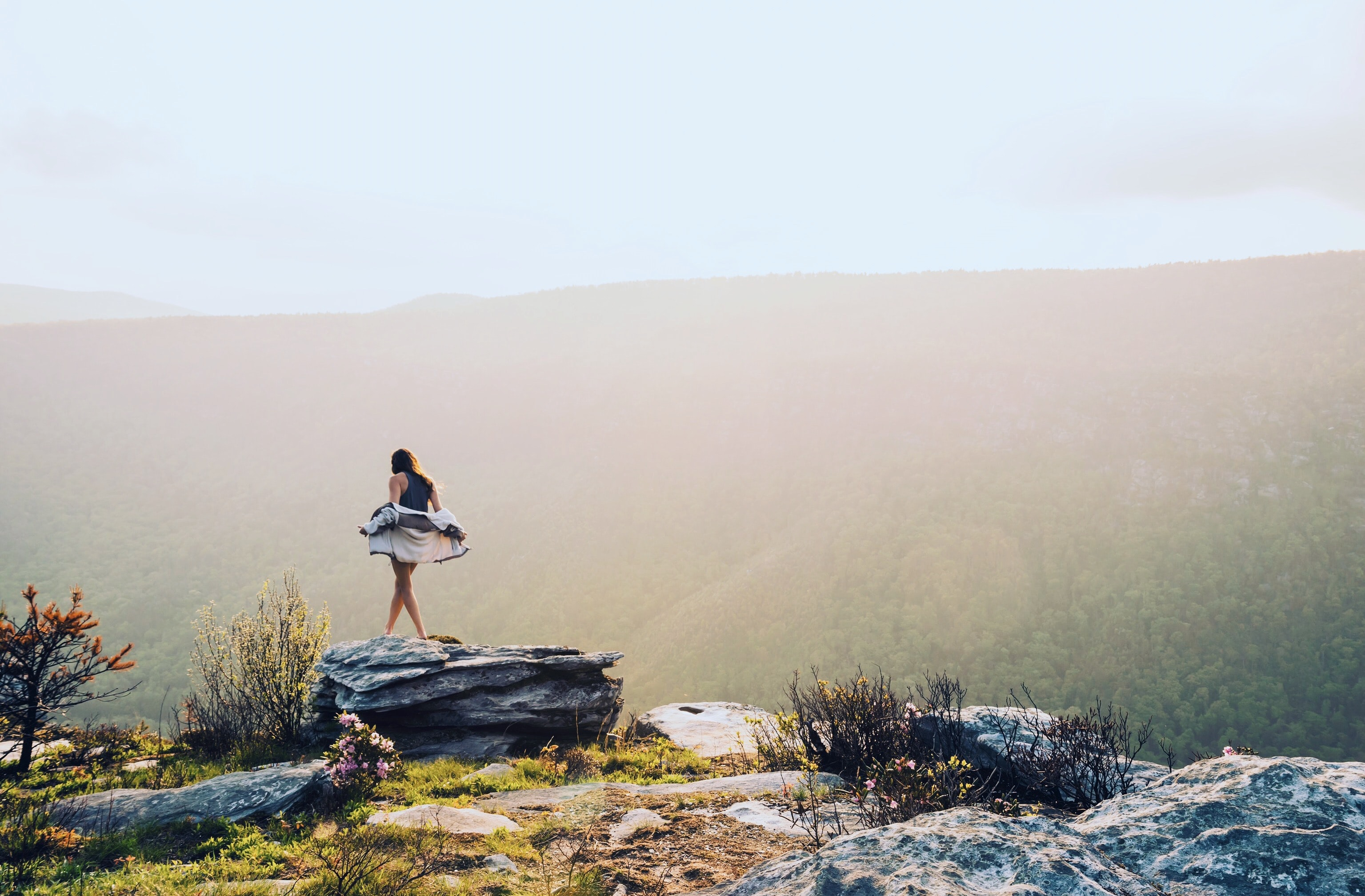 A woman taking off a hoodie on a rock overlooking a wooded valley
