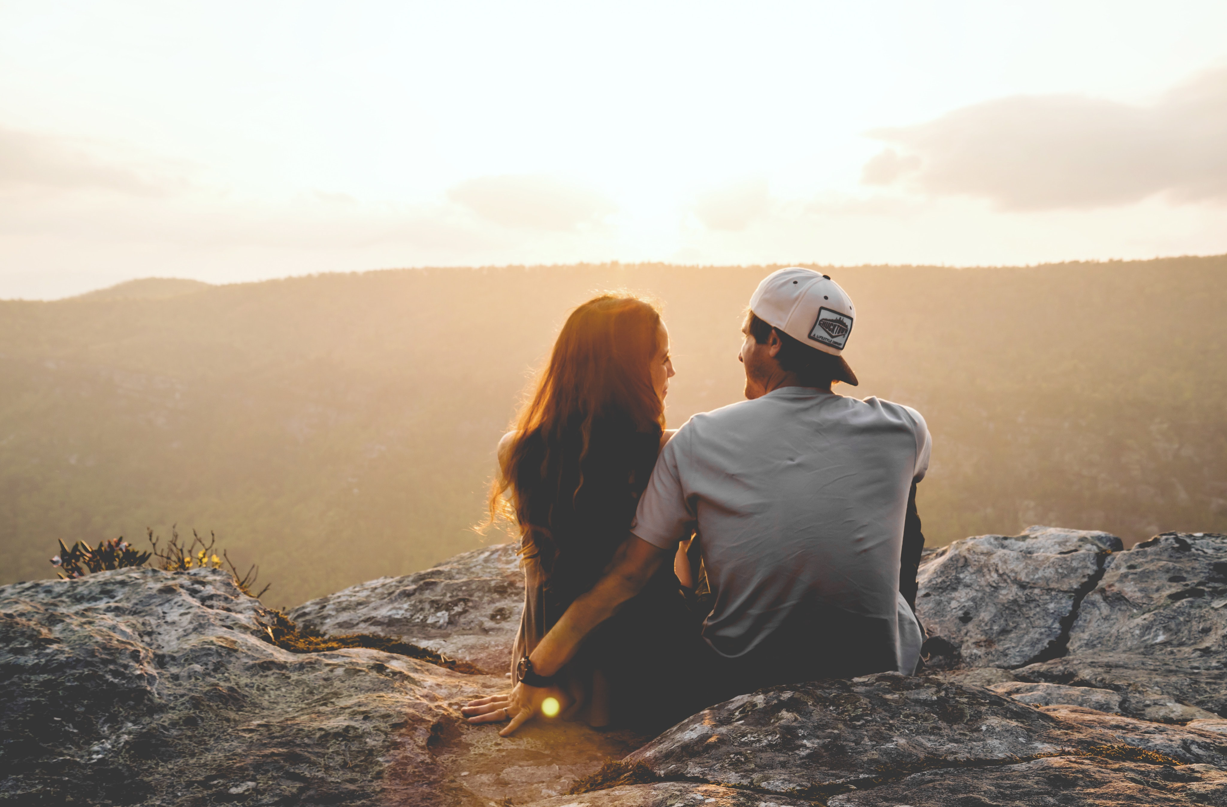 Couple sitting on a rocky mountain looking at each other as sunset colors the sky