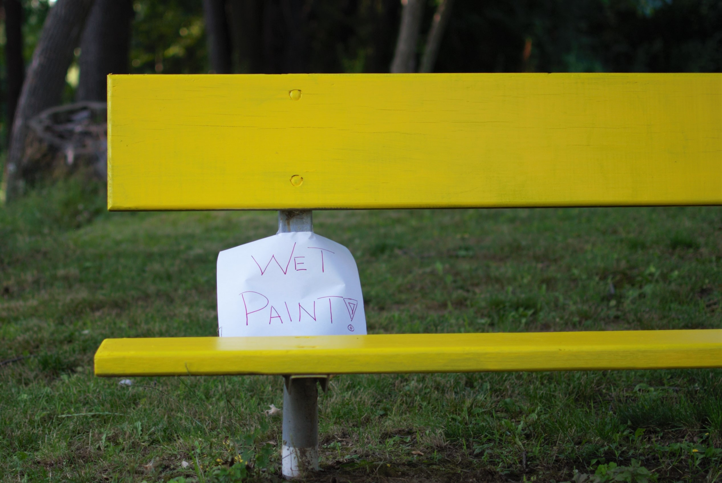 """Wet paint"" sign on a yellow park bench with a fresh coat"