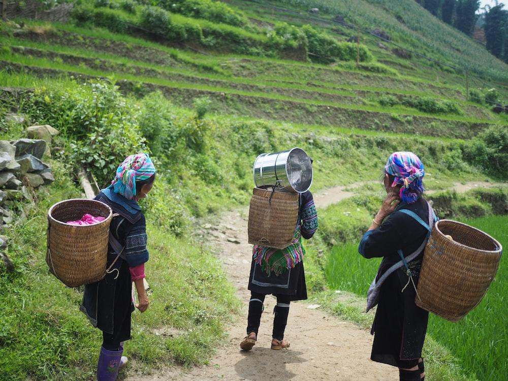 three people wearing brown wicker baskets walking on road