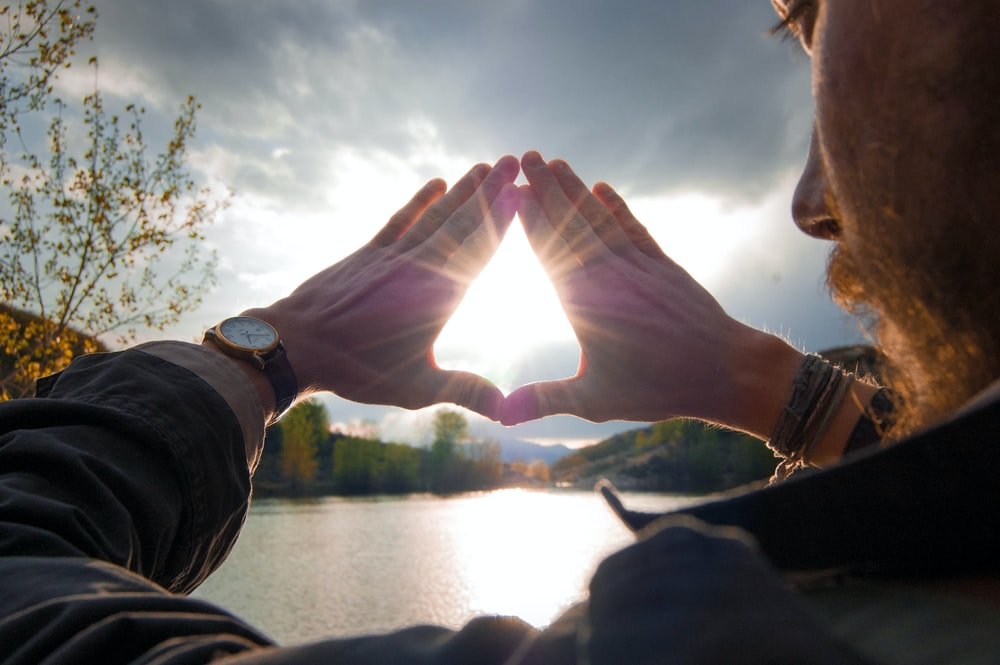 A bearded man beside a lake holds his hands in a triangle, the sun shining through