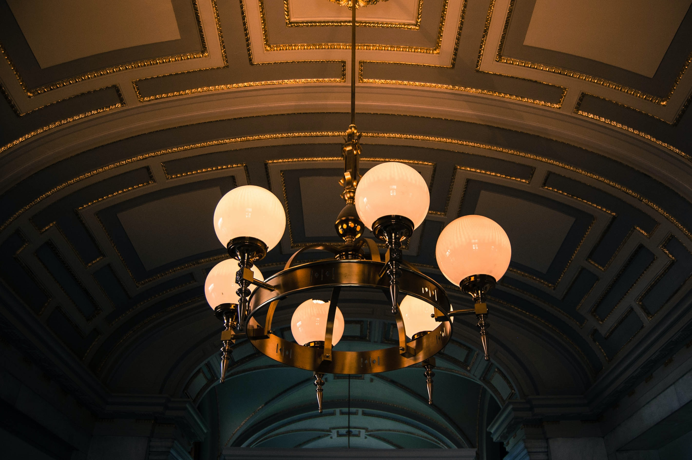 Incandescent globe bulbs on a gold chandelier hanging from an ornate ceiling