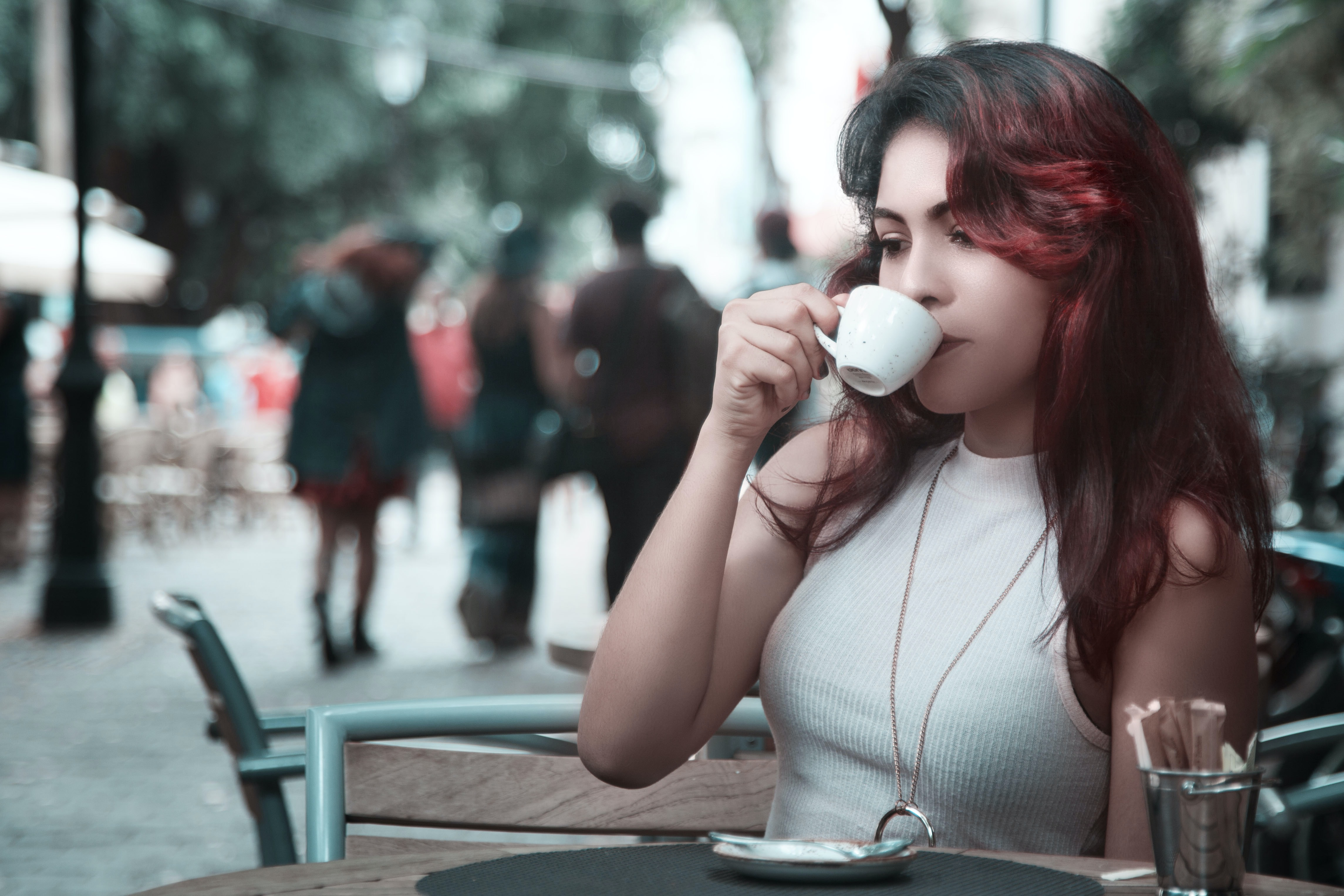 A woman with dyed red hair sips from a teacup at an outdoor cafe table