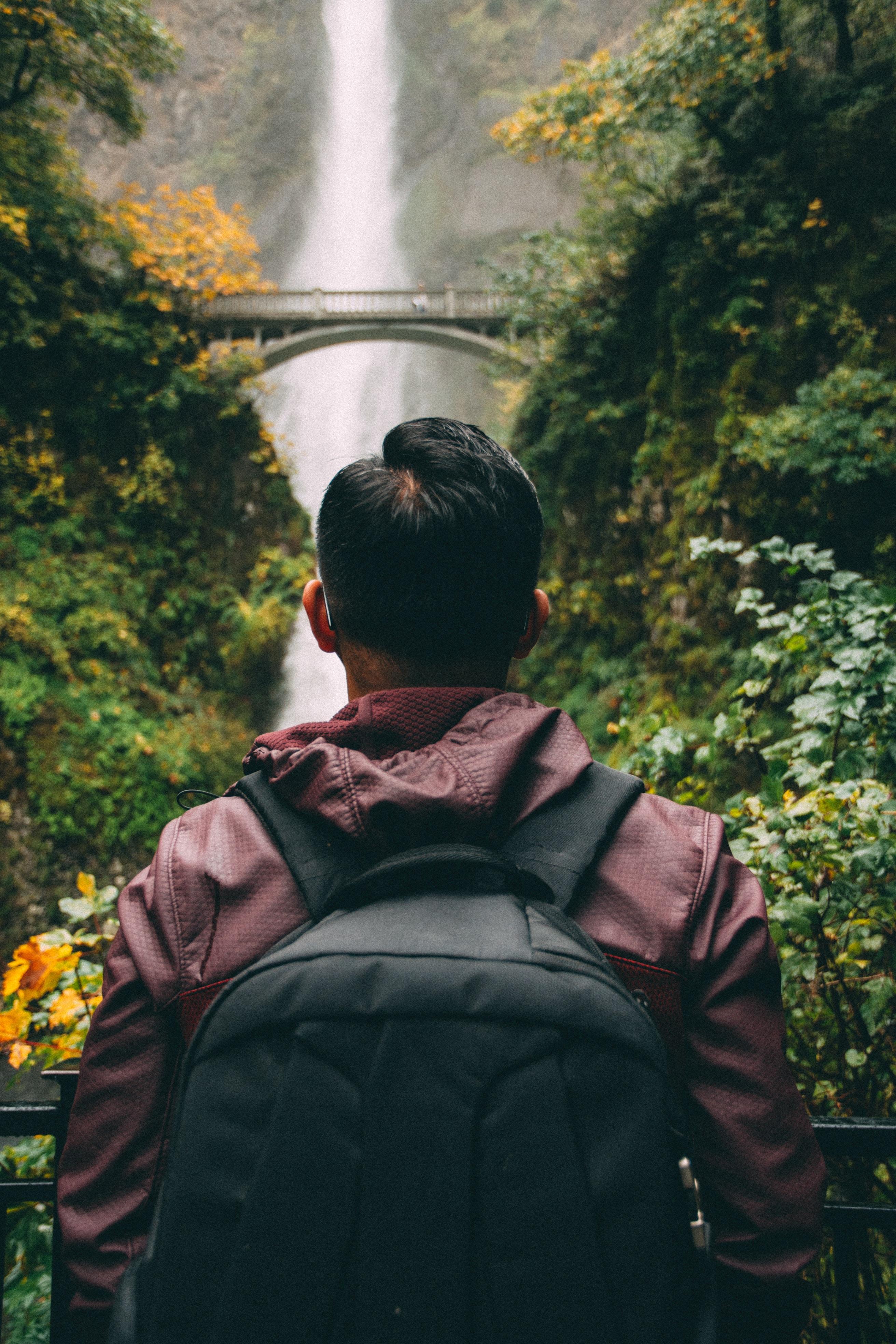 Backpacker hikes alone towards a waterfall behind a bridge