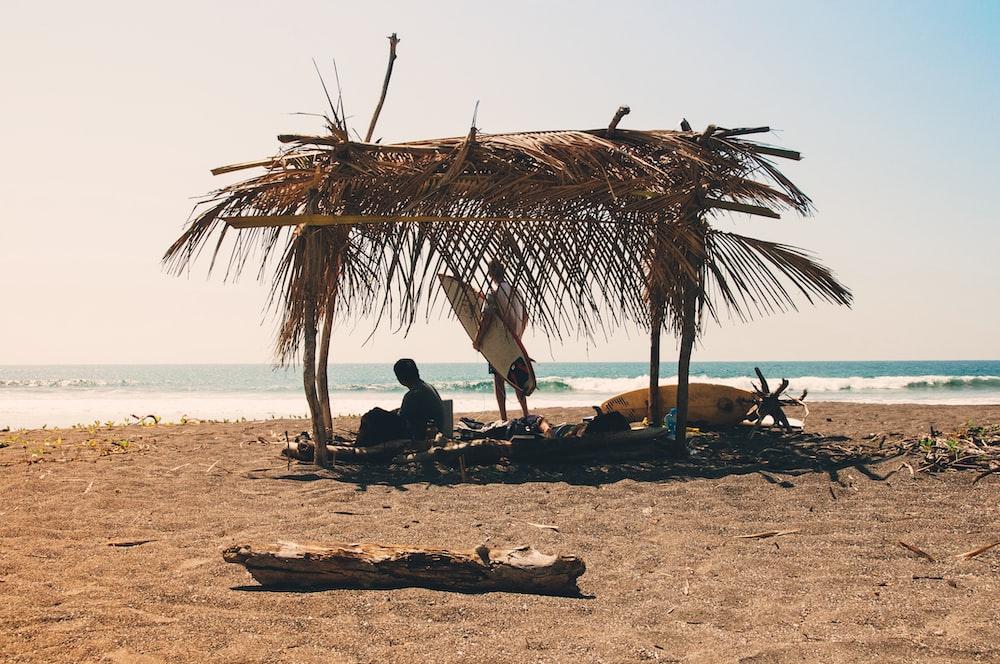 man reclining under hut on seashore