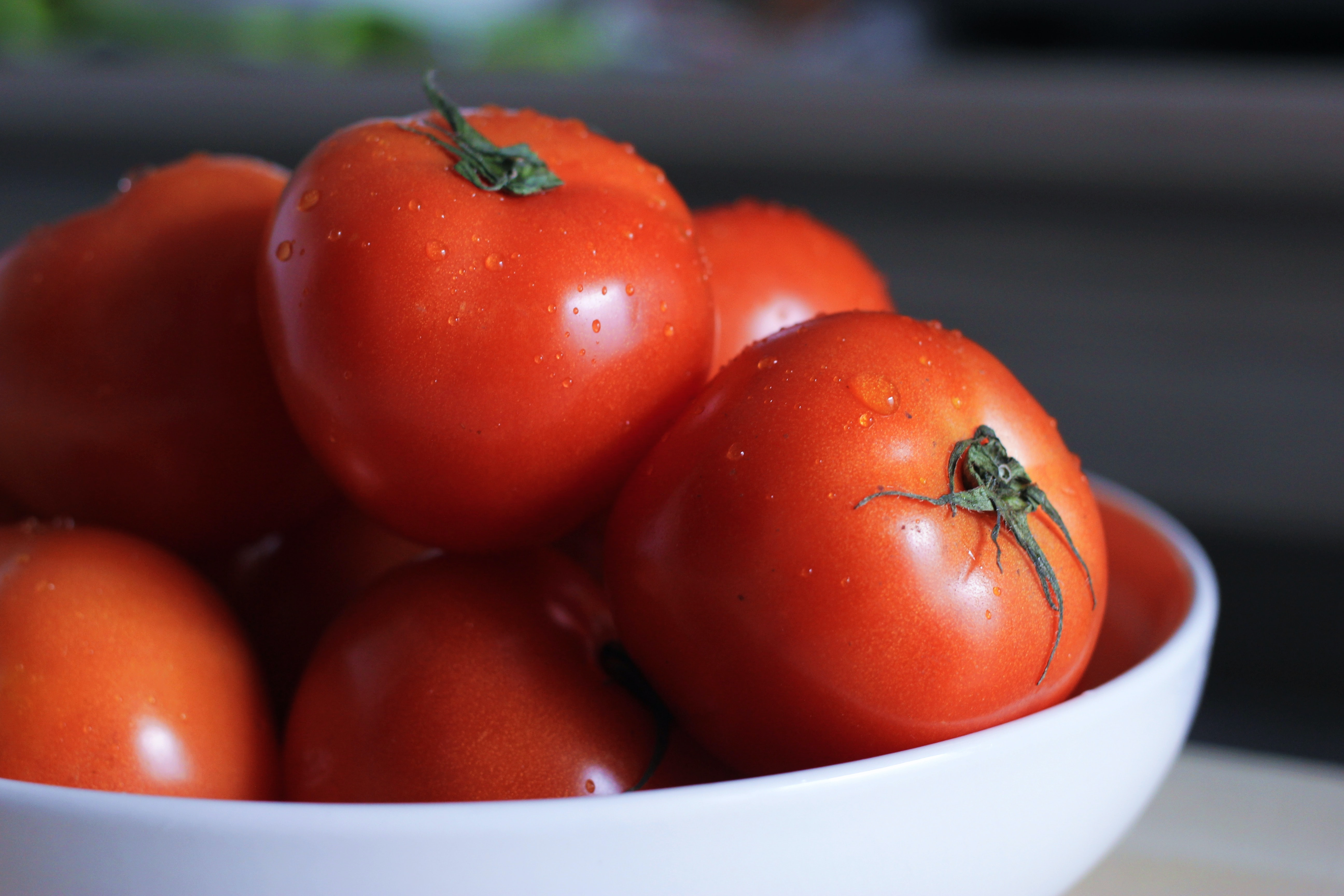 Freshly washed tomatoes in a white bowl ready to eat