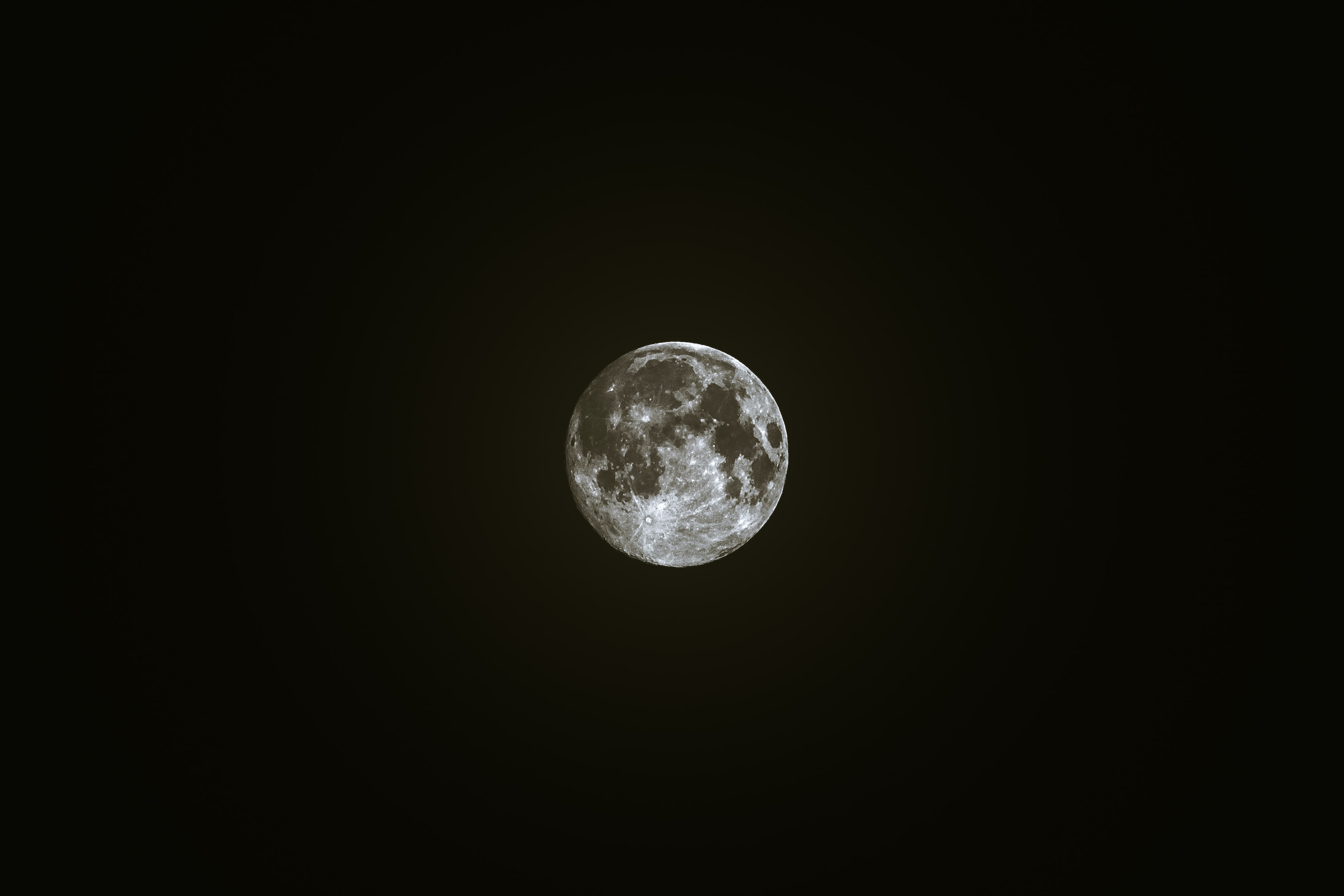 Black and white shot of glowing moon on black sky