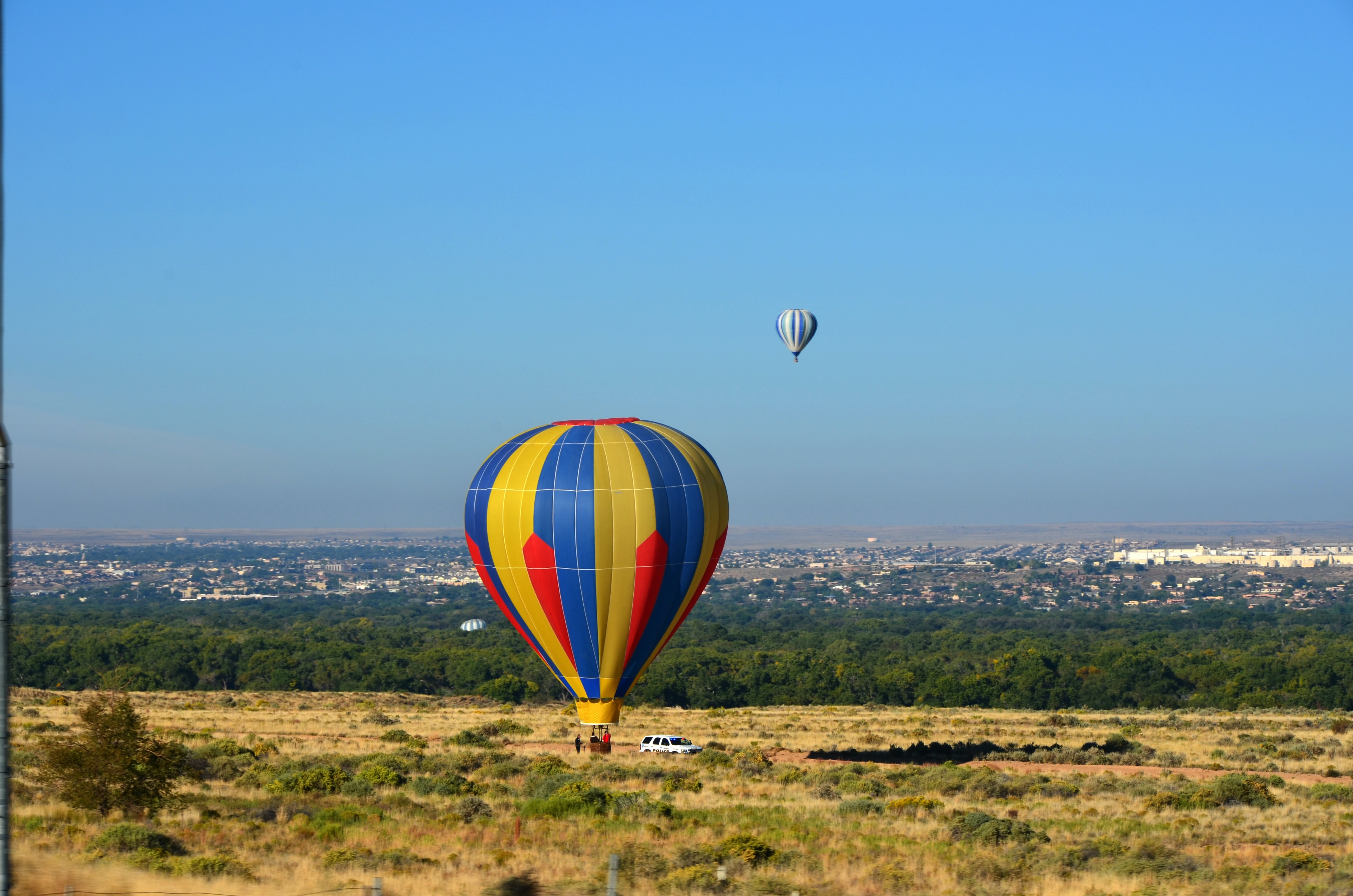 Red, blue, yellow hot air balloon resting on ground with another hot air balloon in distance