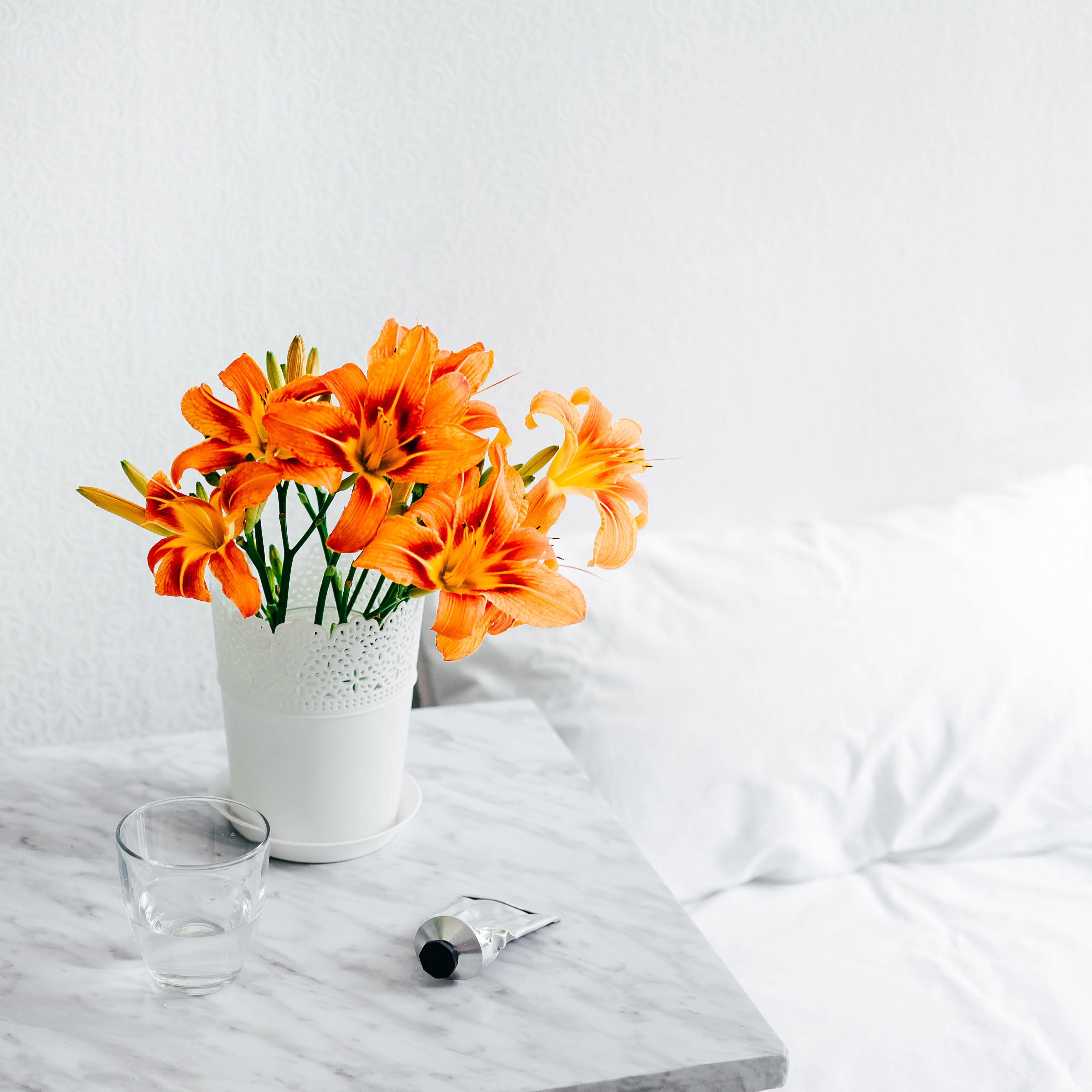 A bouquet of Tiger Lily's on a marble table next to a bed