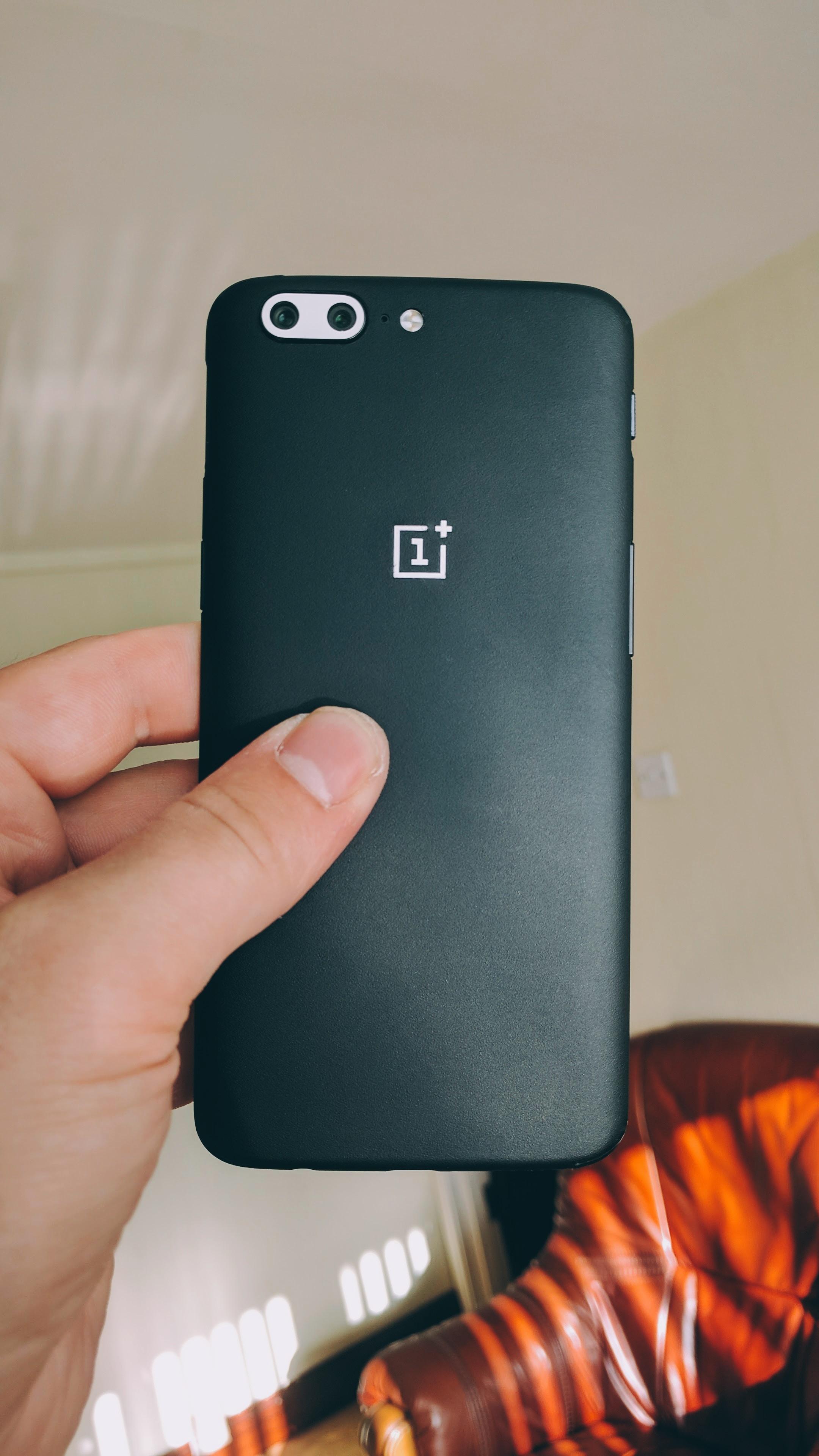 Holding a black smartphone.