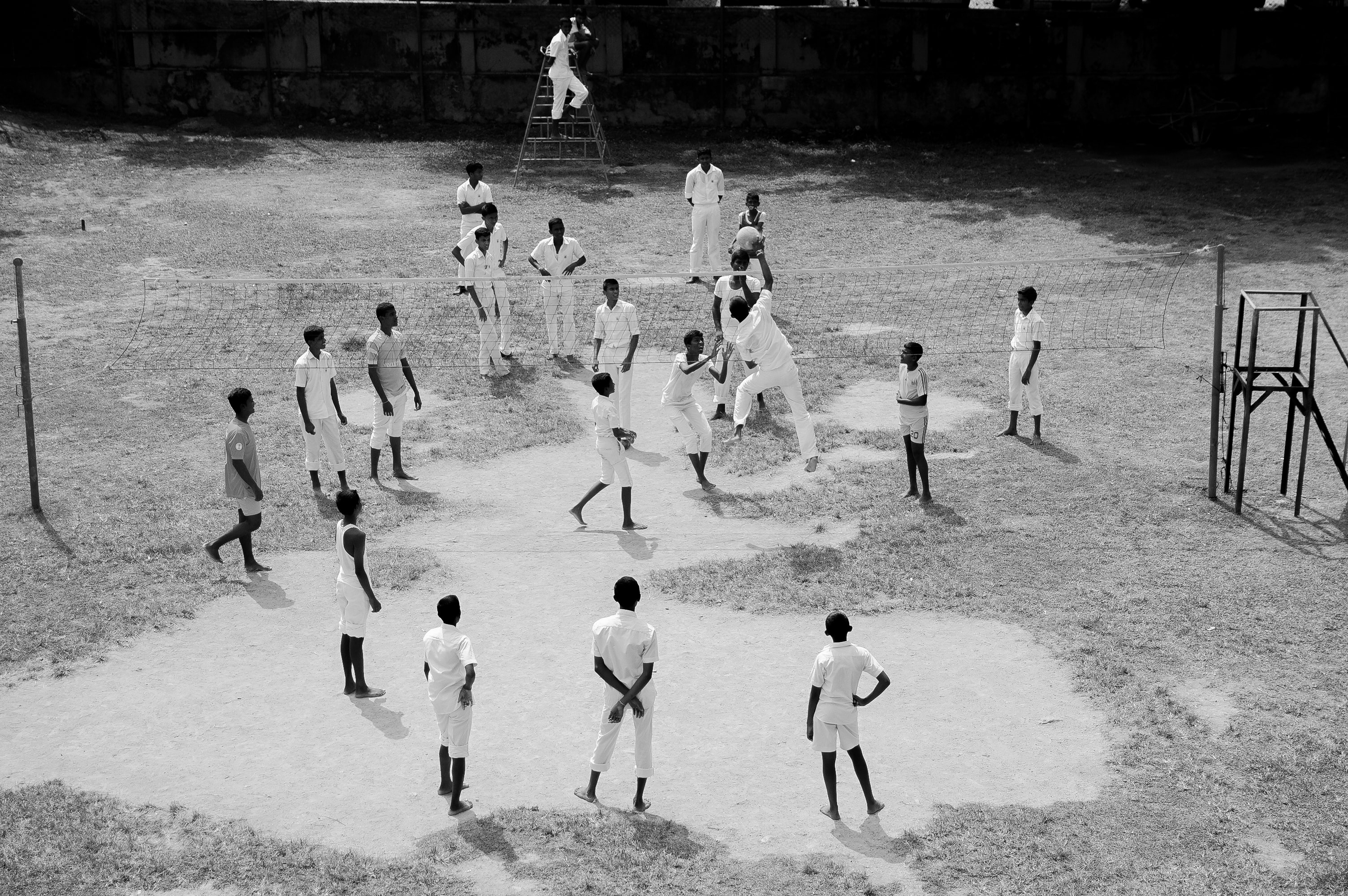 Black and white shot of people playing volleyball in white uniforms on dusty ground, Sri Lanka