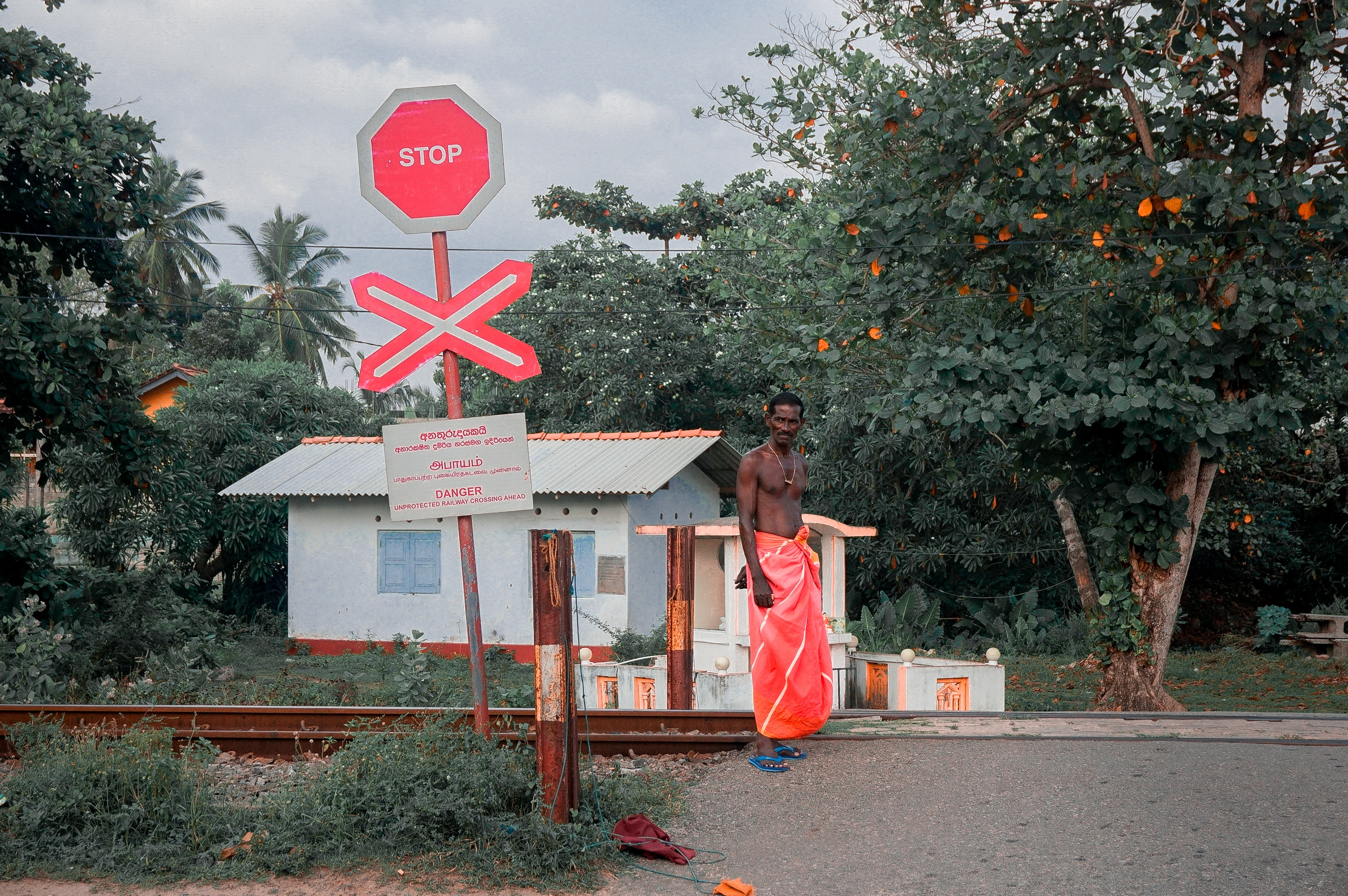 A man wrapped in a sarong stands by a stop sign along railway tracks and trees