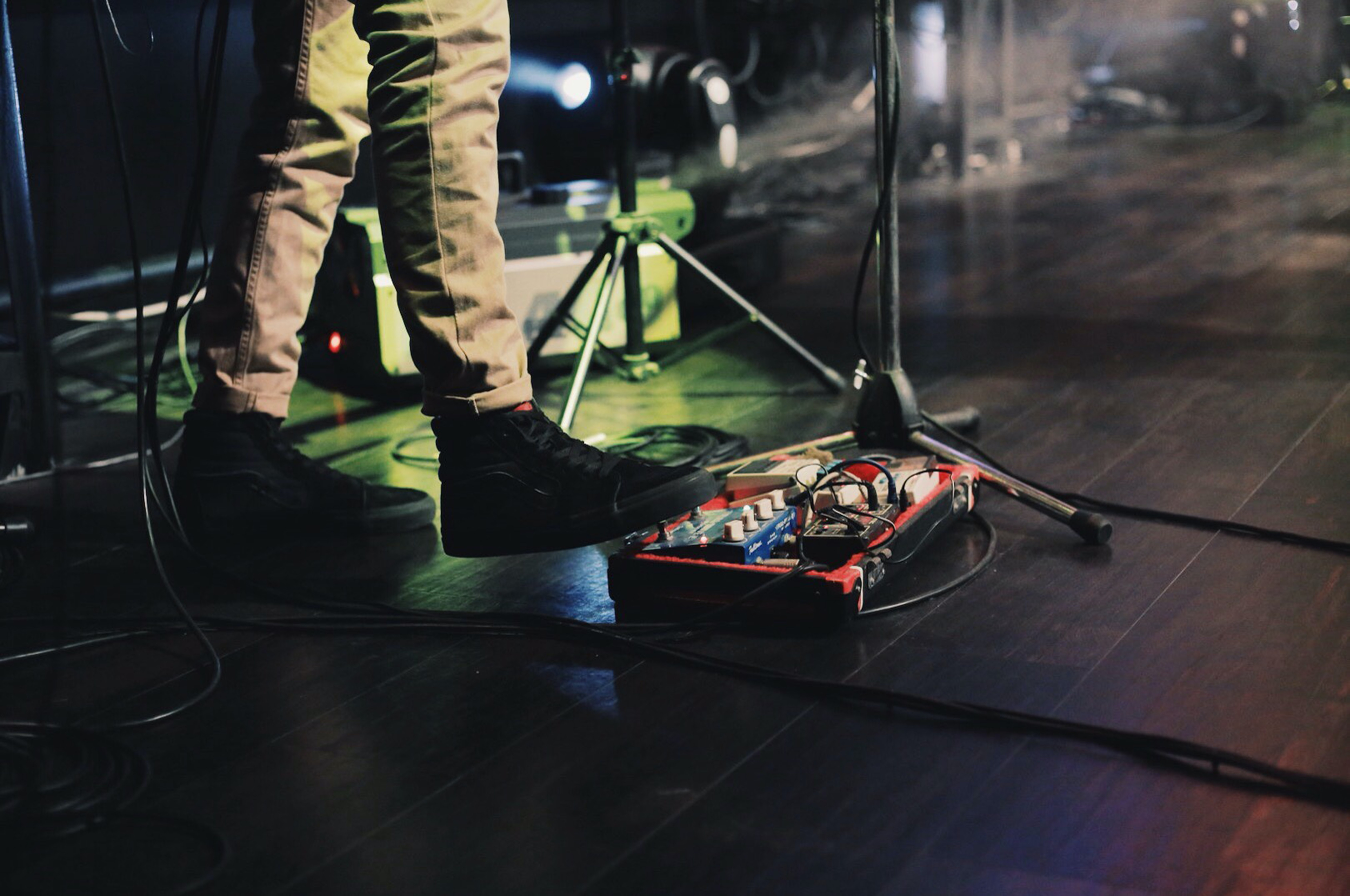 A musician on stage flipping a switch with his foot