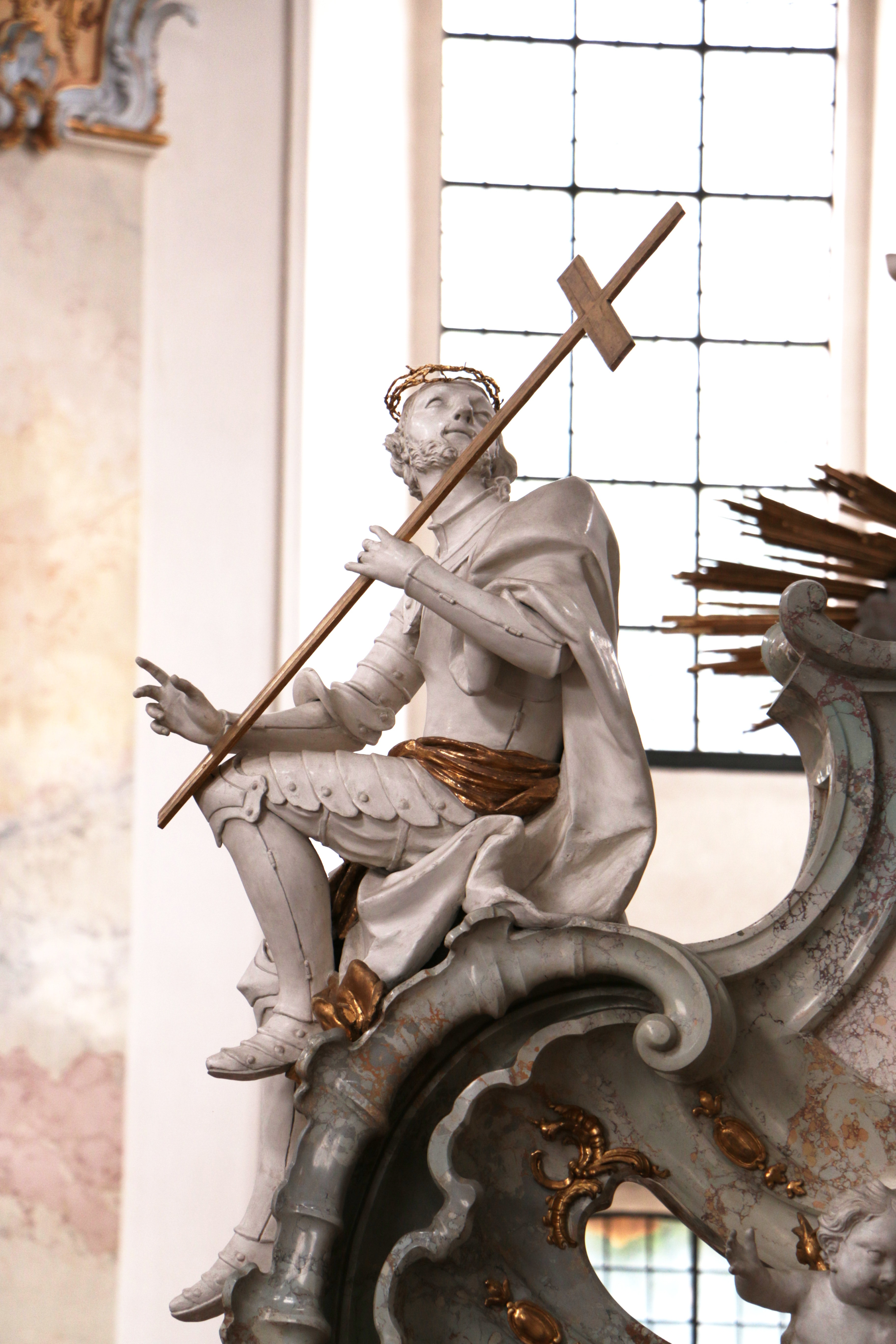 A sculpture of a warrior carrying a cross sitting on the corner of a mantelpiece while looking up