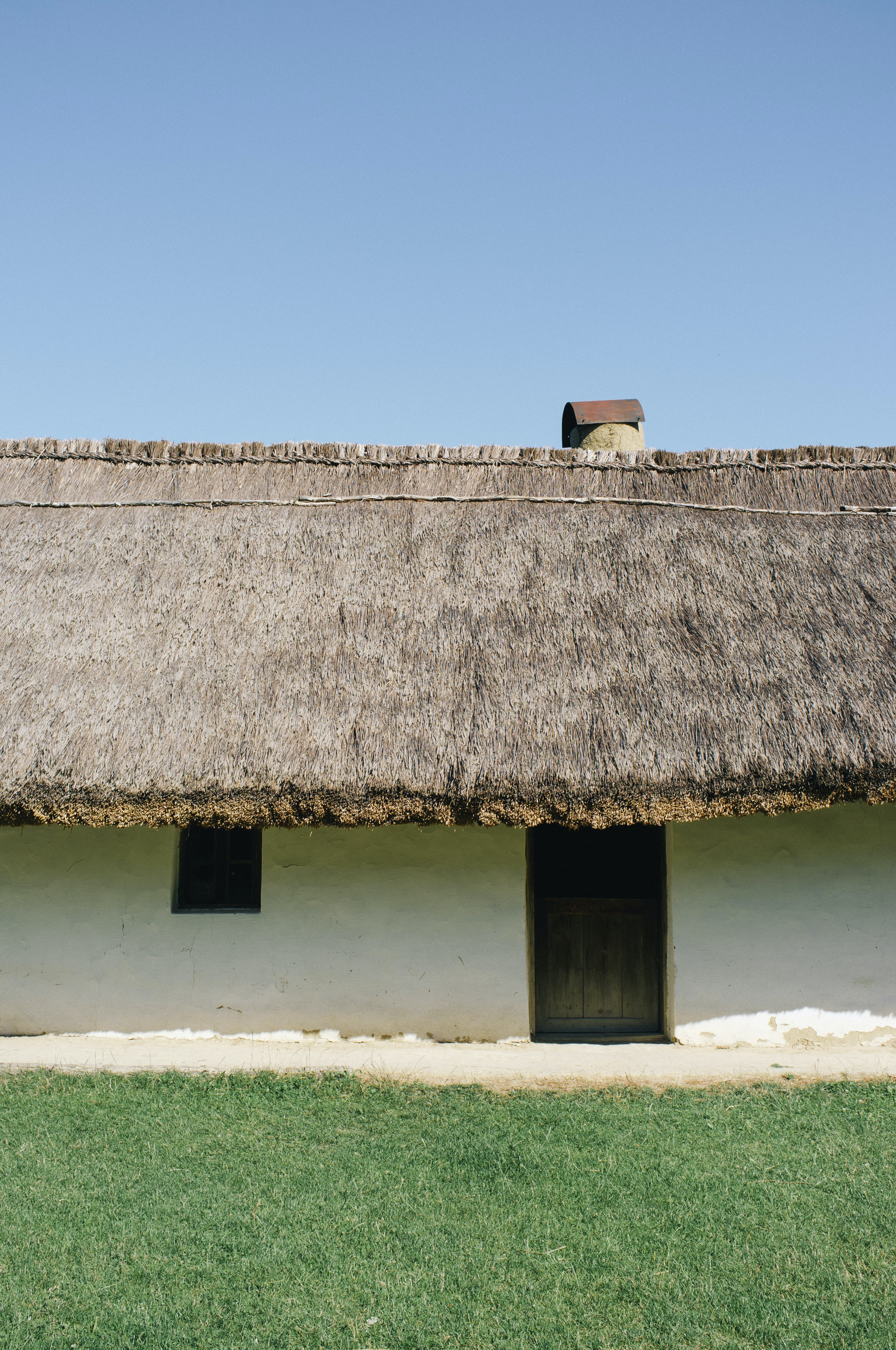 Thatched roof house with green grass lawn under blue skies