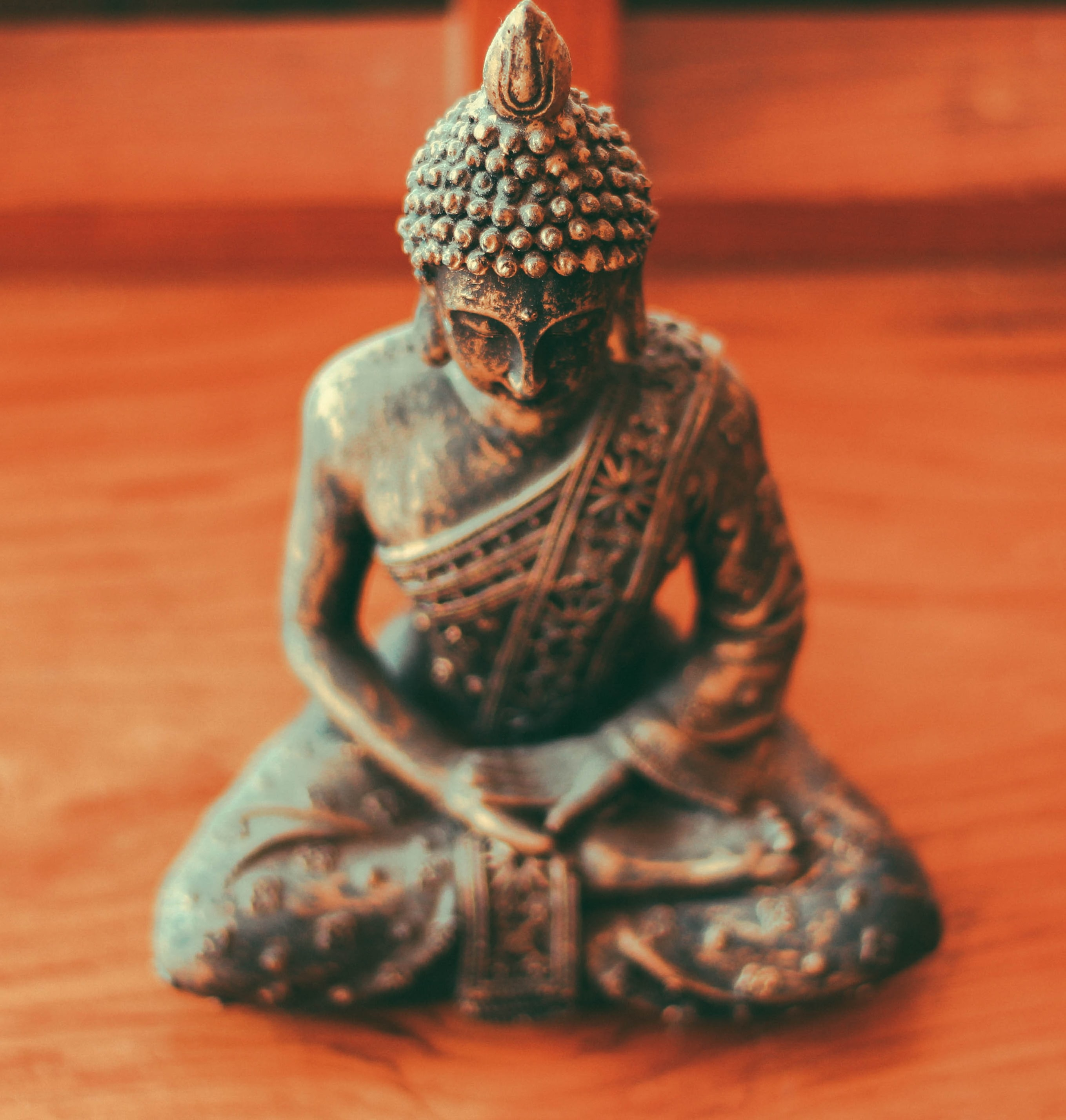 Gautama Buddha figurine on brown wooden surface