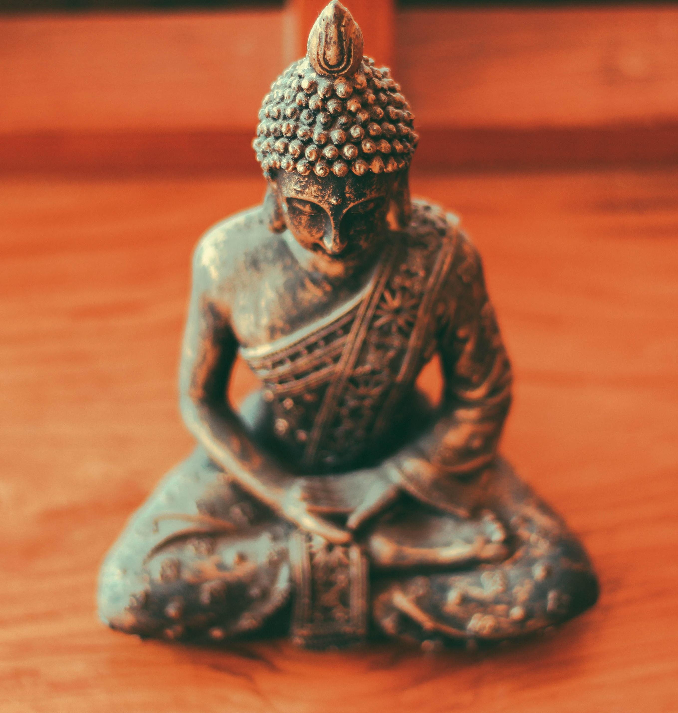 Gautama Buddha figurine on brown wooden surface