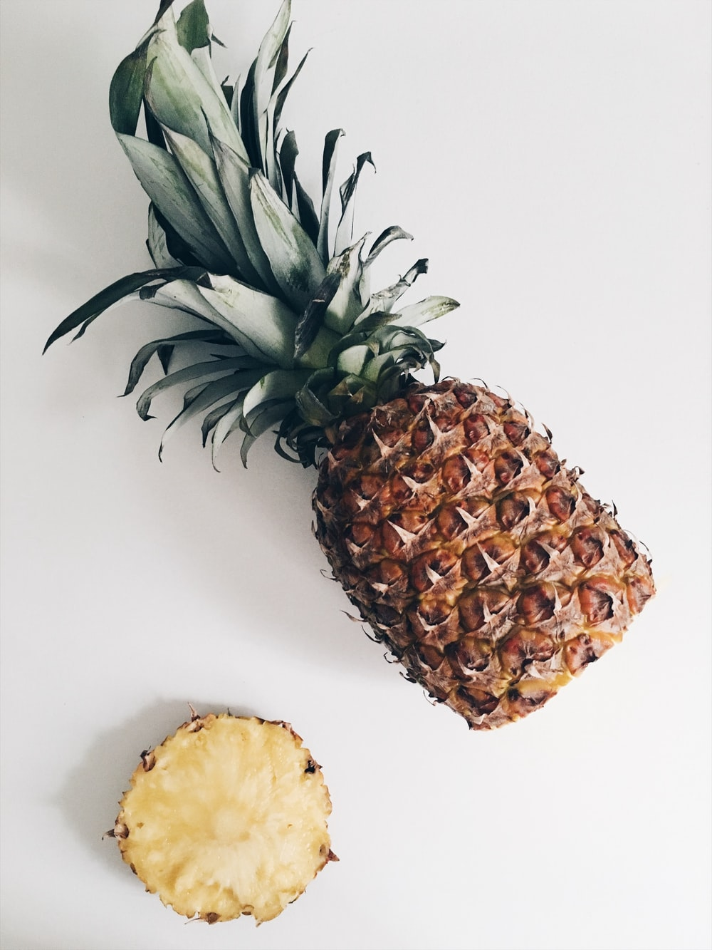A pineapple lying on its side with its bottom sliced off.