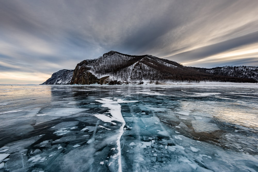 melting ice on water near gray mountain at daytime