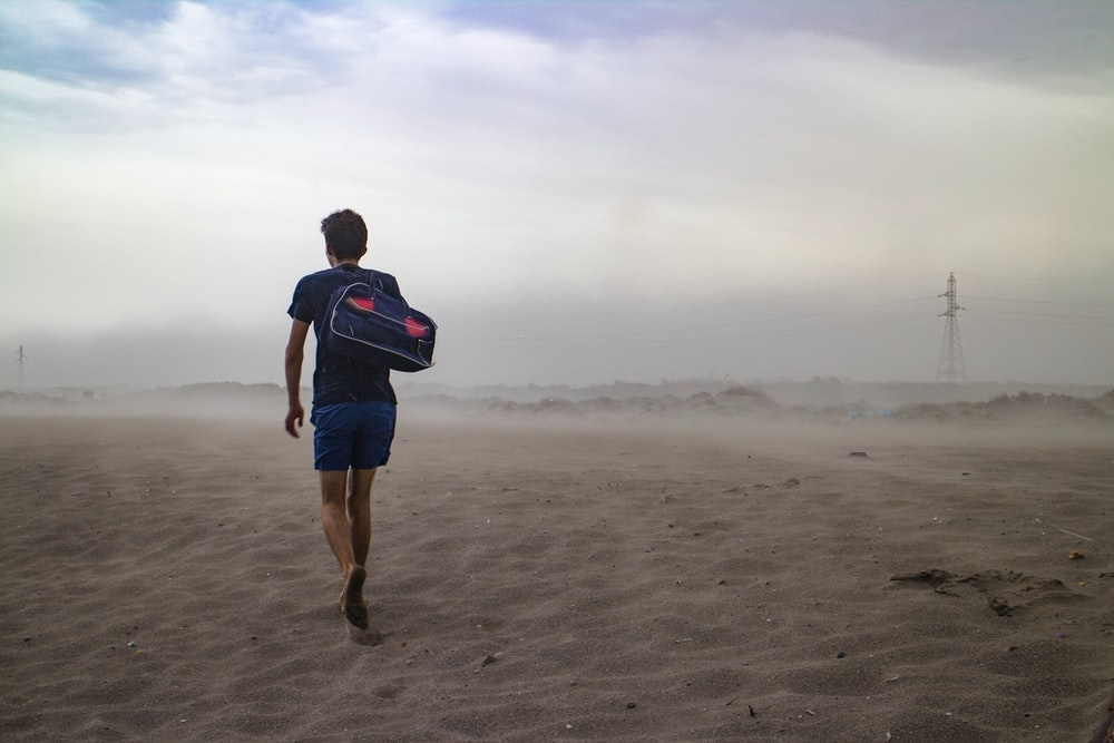 man wearing black t-shirt and blue short carrying black duffel bag on shoulder in the middle of desert