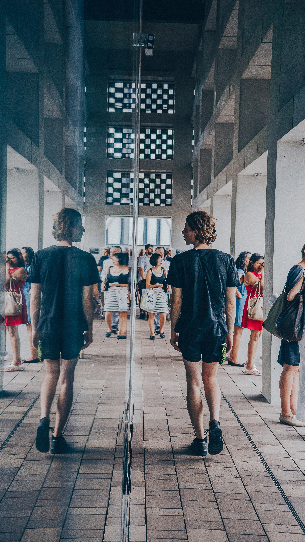 man walking beside mirror wall building