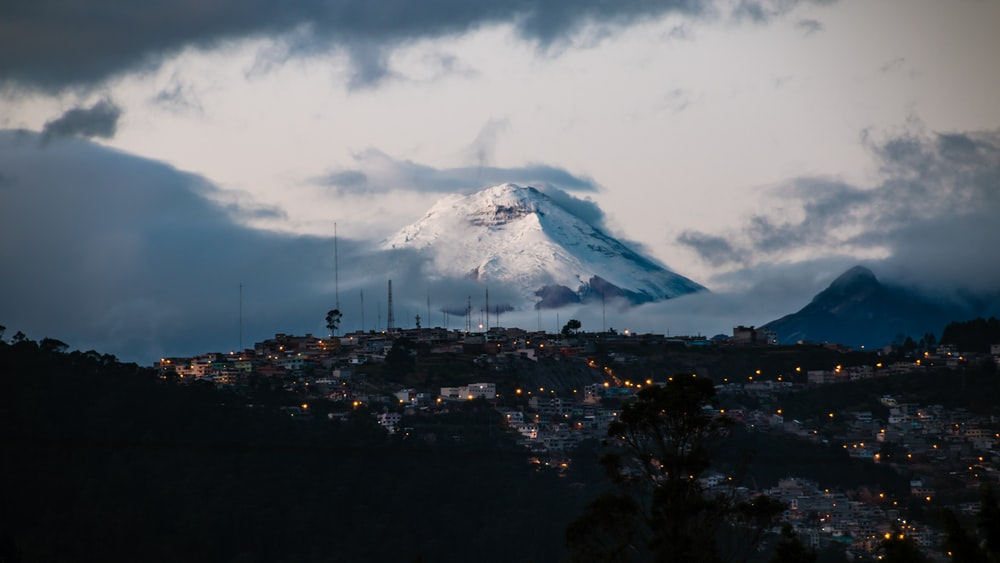 town with lights far from mountain field with snow