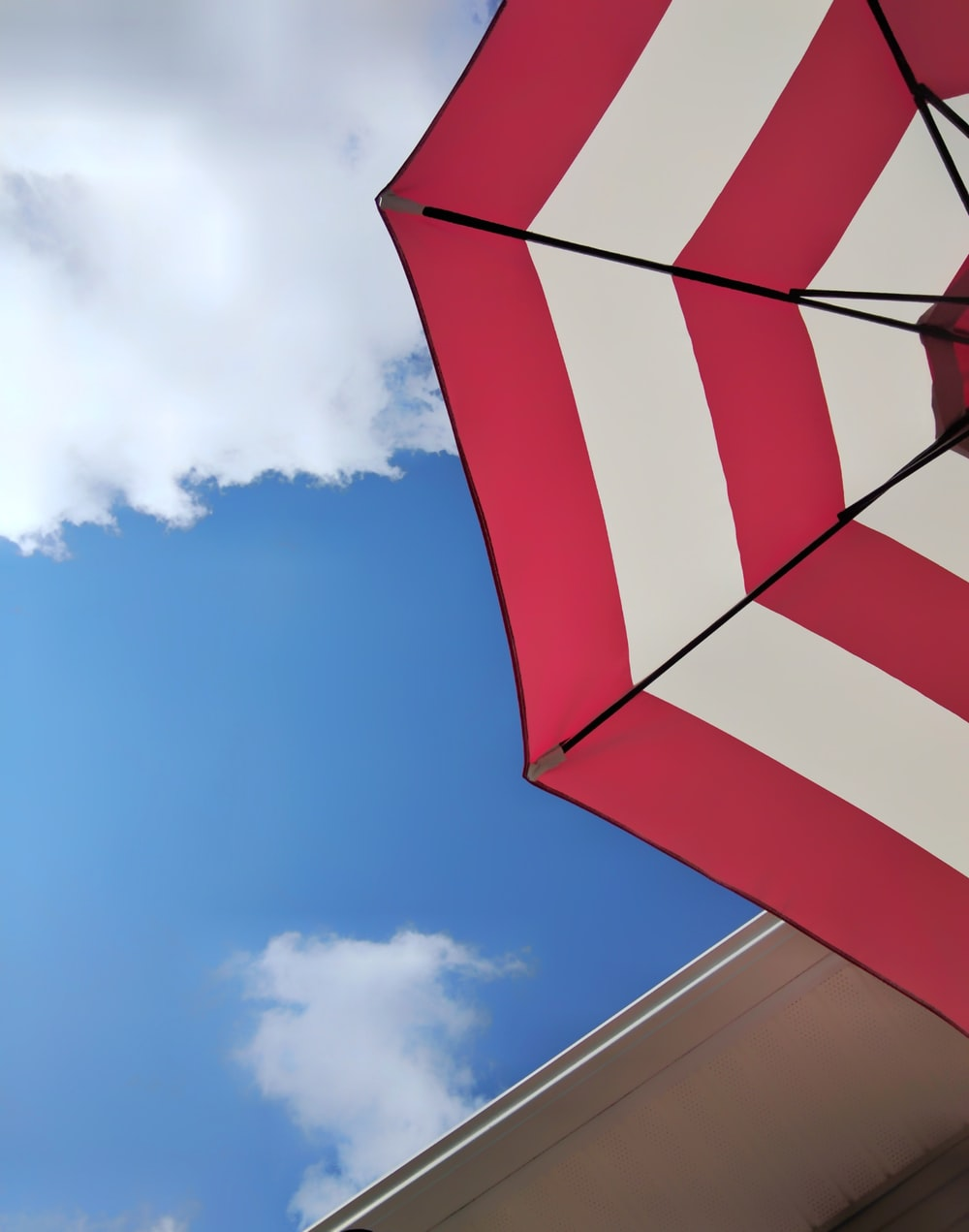 low angle photography of red and white umbrella