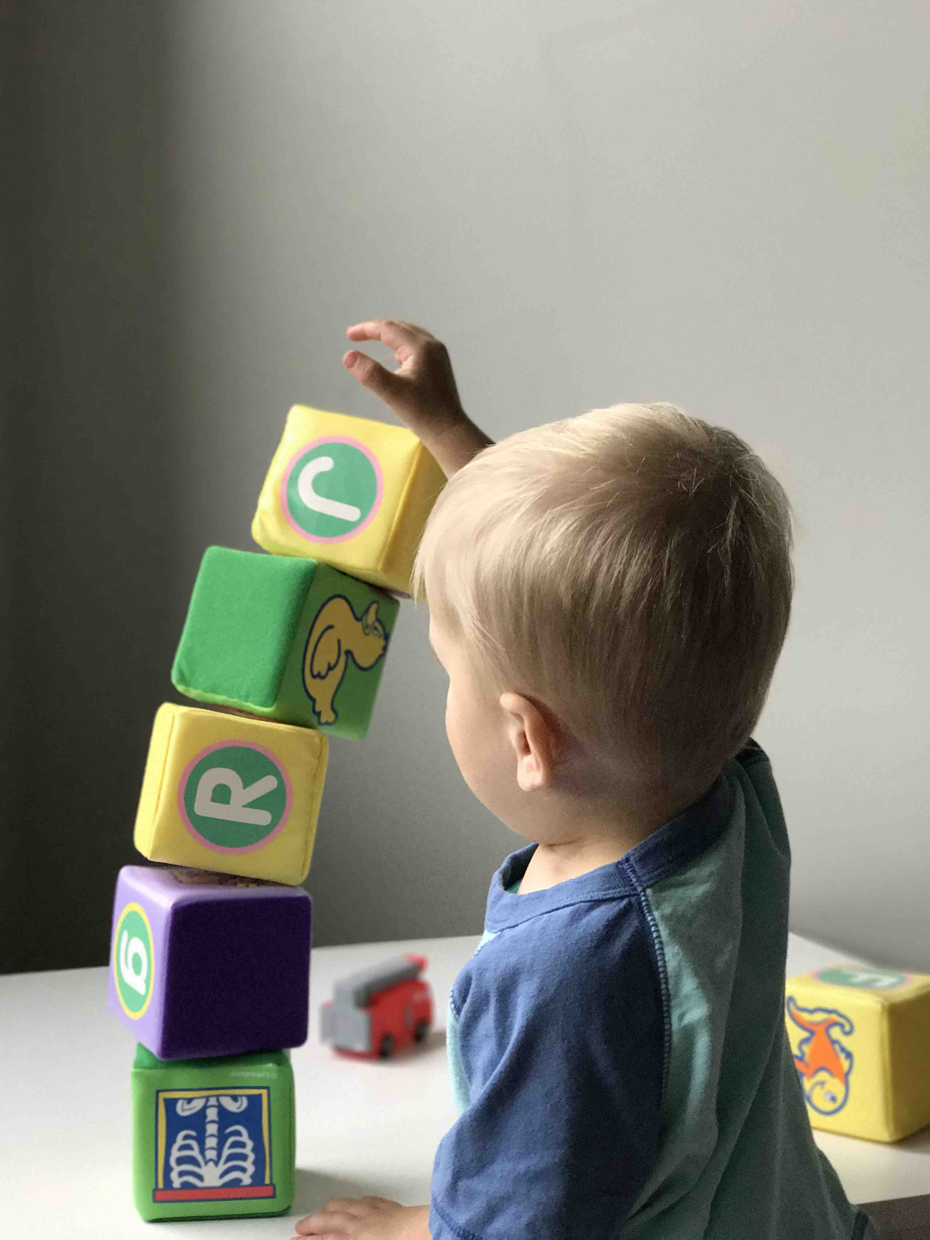A baby builds a stack of blocks, which begins to fall over onto the table