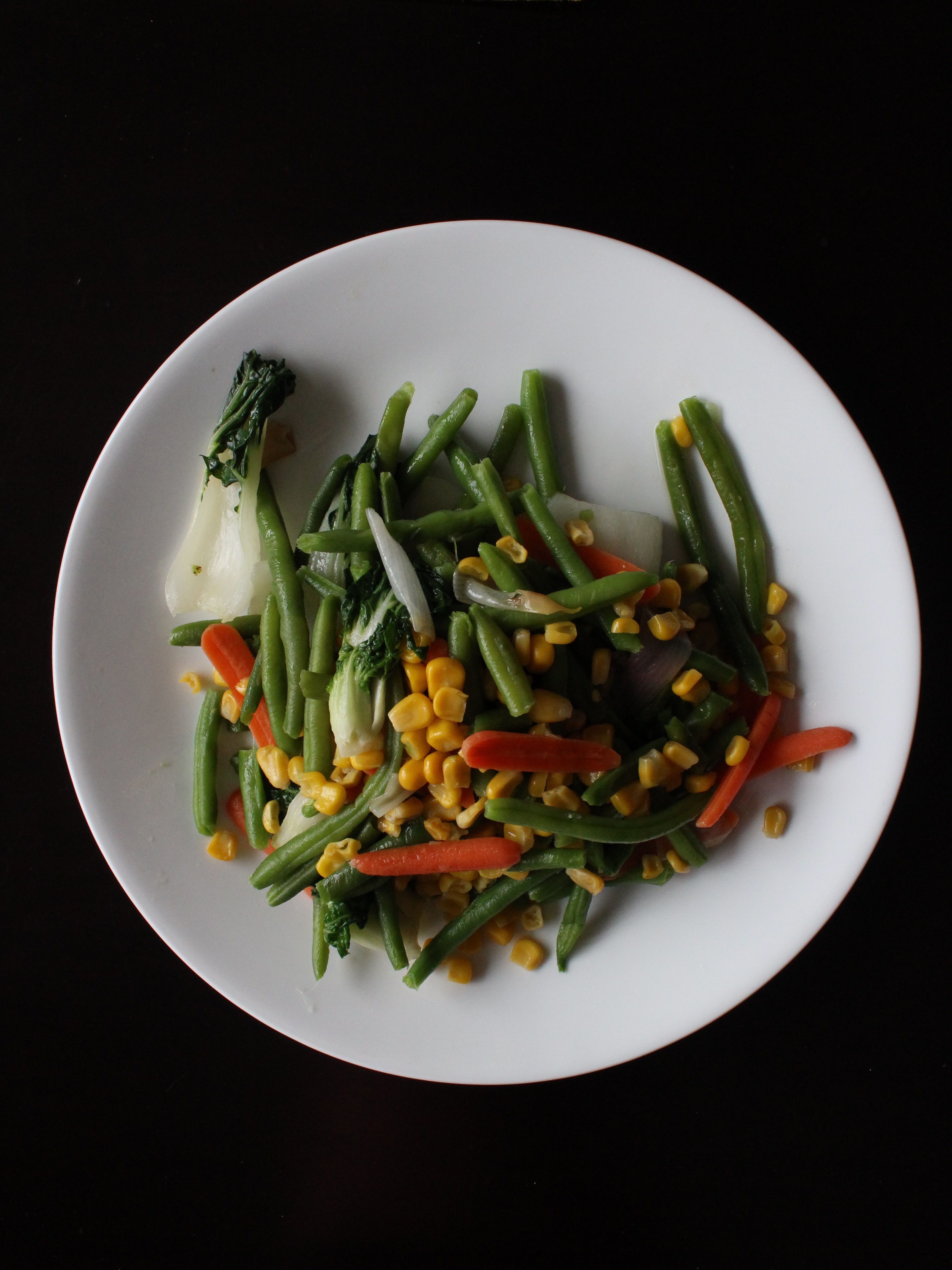 A white plate full of green beans, corn, carrots, and bok choy
