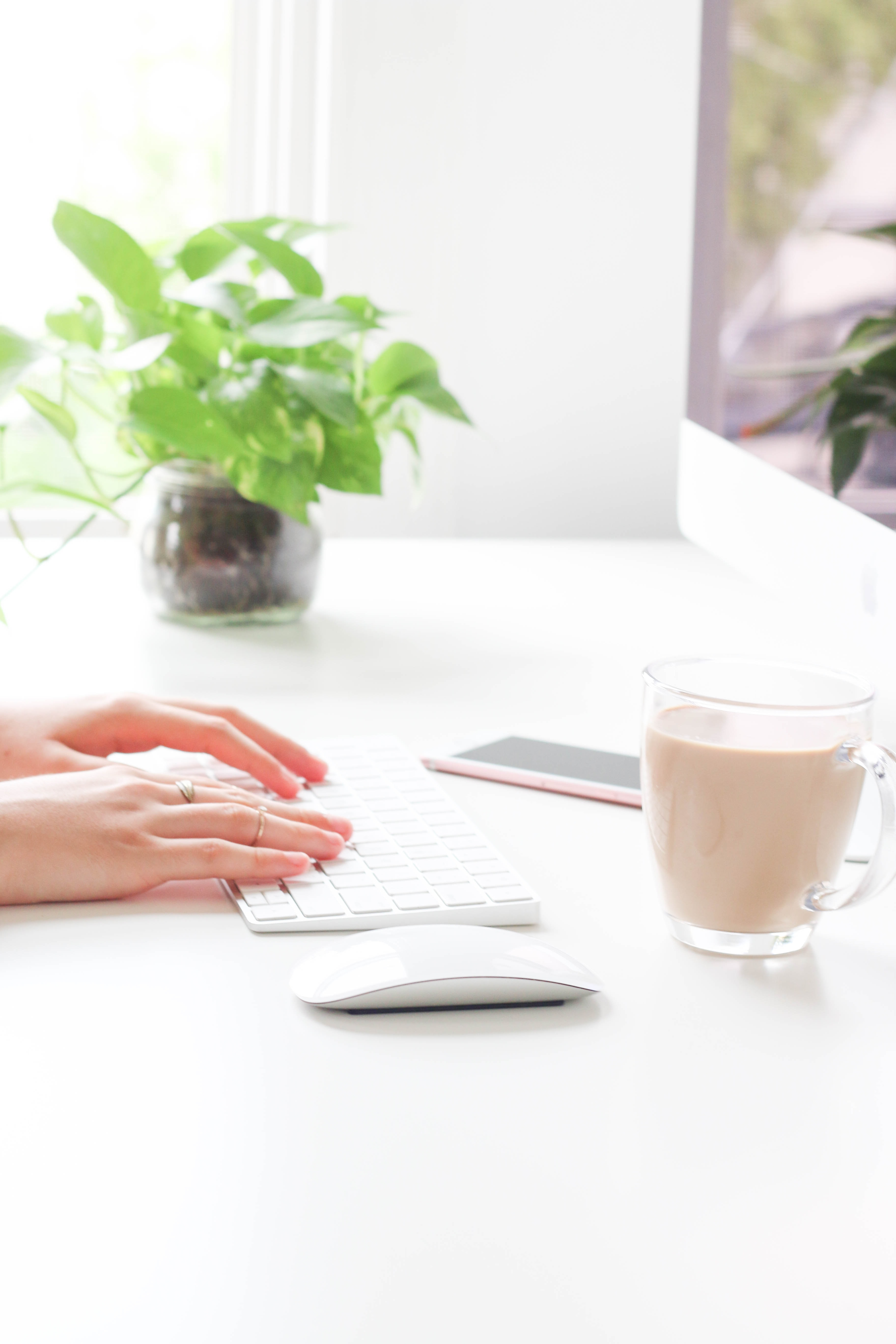 A person's hands on a laptop keyboard on a white desk with a glass of coffee
