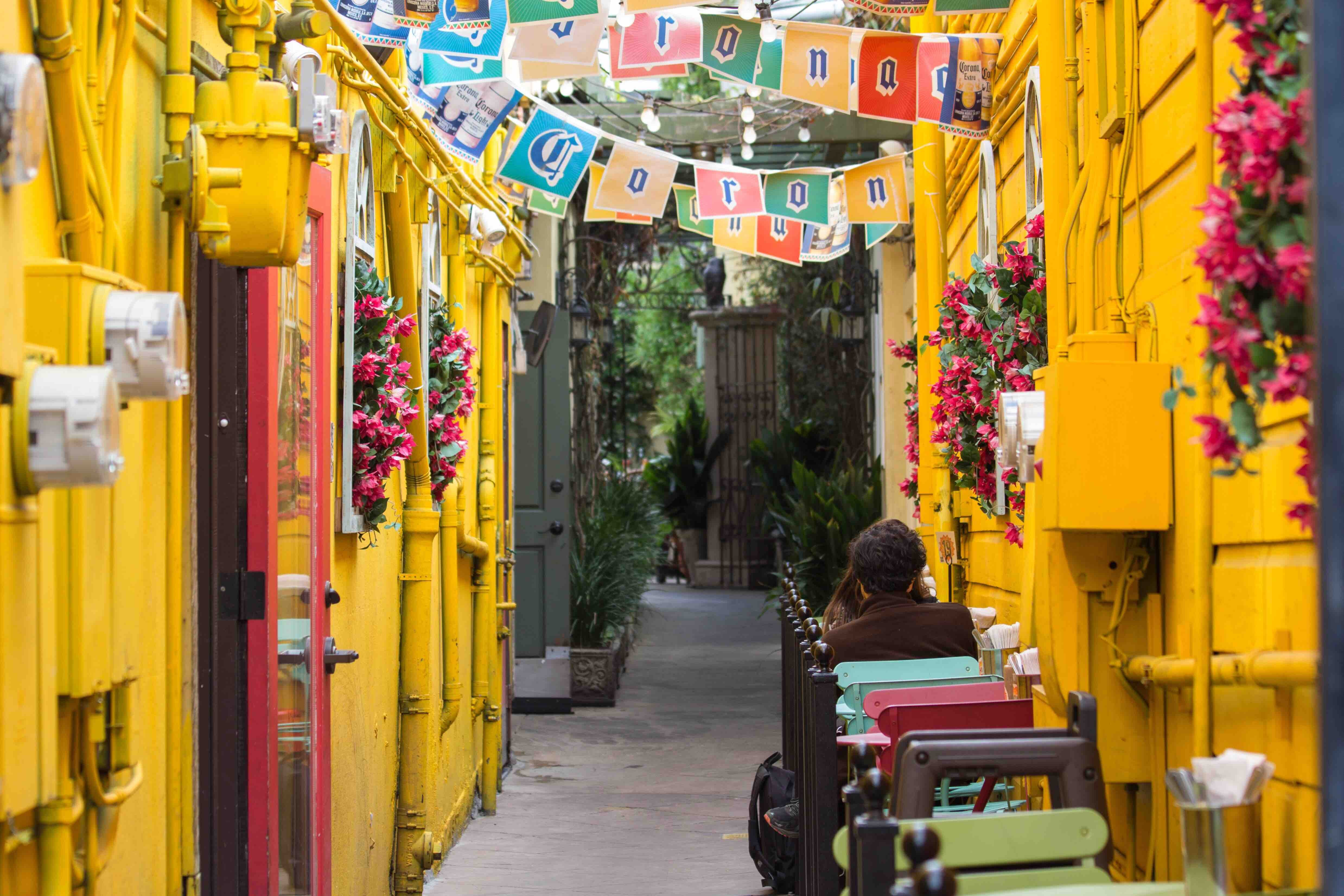 An alley between yellow walls and buildings and people sitting in a cafe under a festival decorations