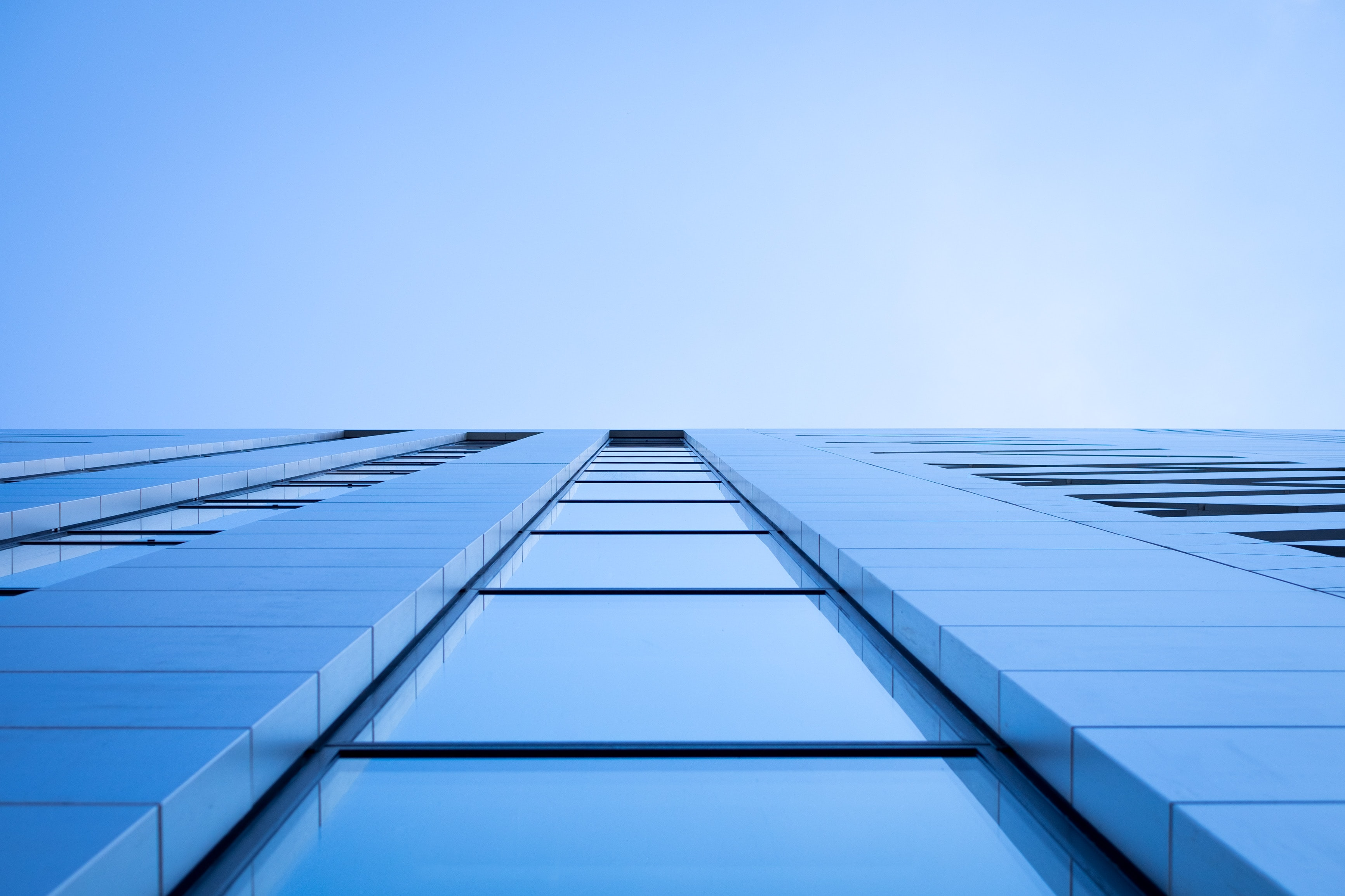 A low-angle shot of a the windows in a tall office building