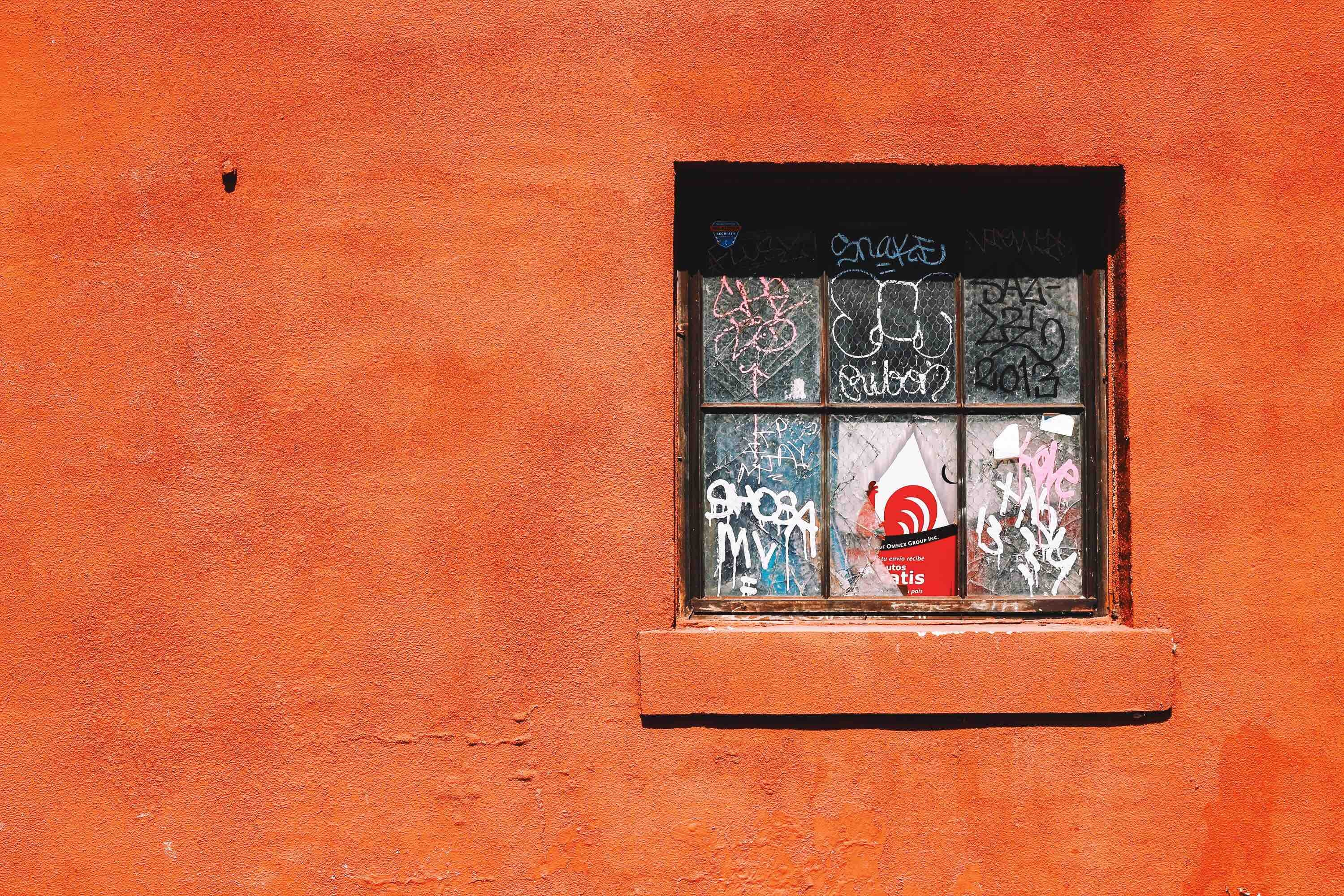 Graffiti on a broken old window in a red-painted building