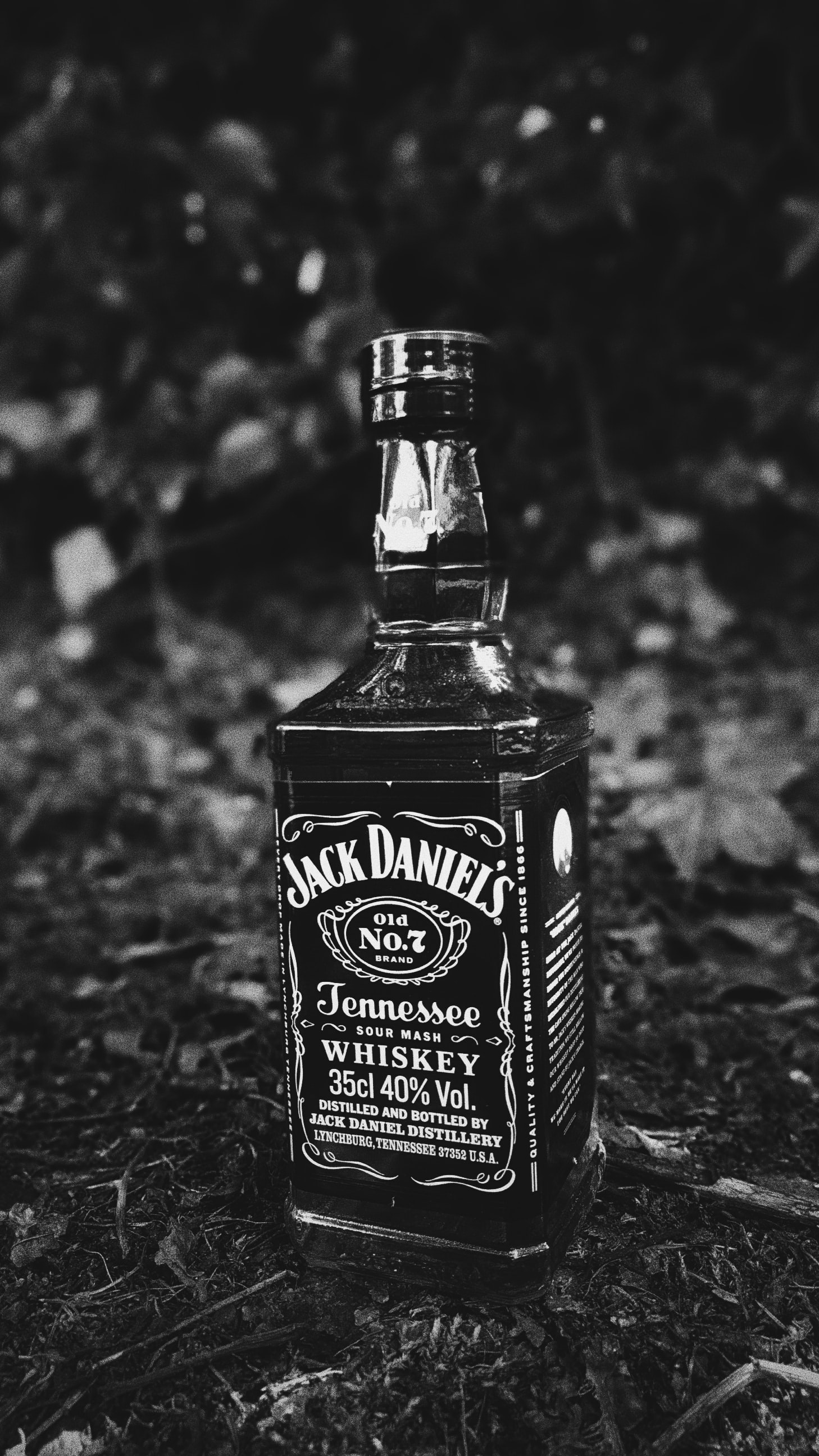Black and white macro shot of bottle of Jack Daniels outdoor on the ground