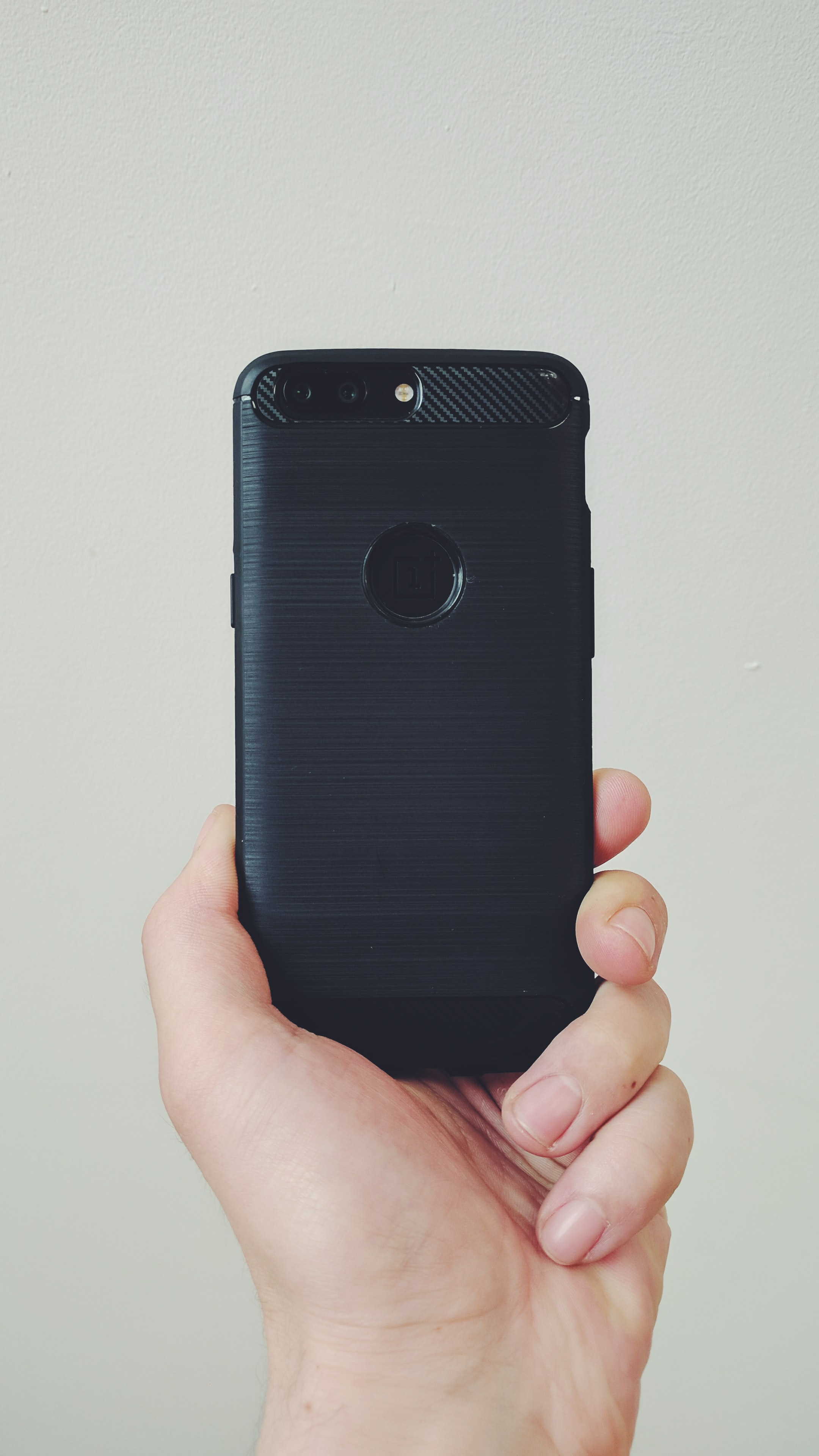 A person holding black phone.