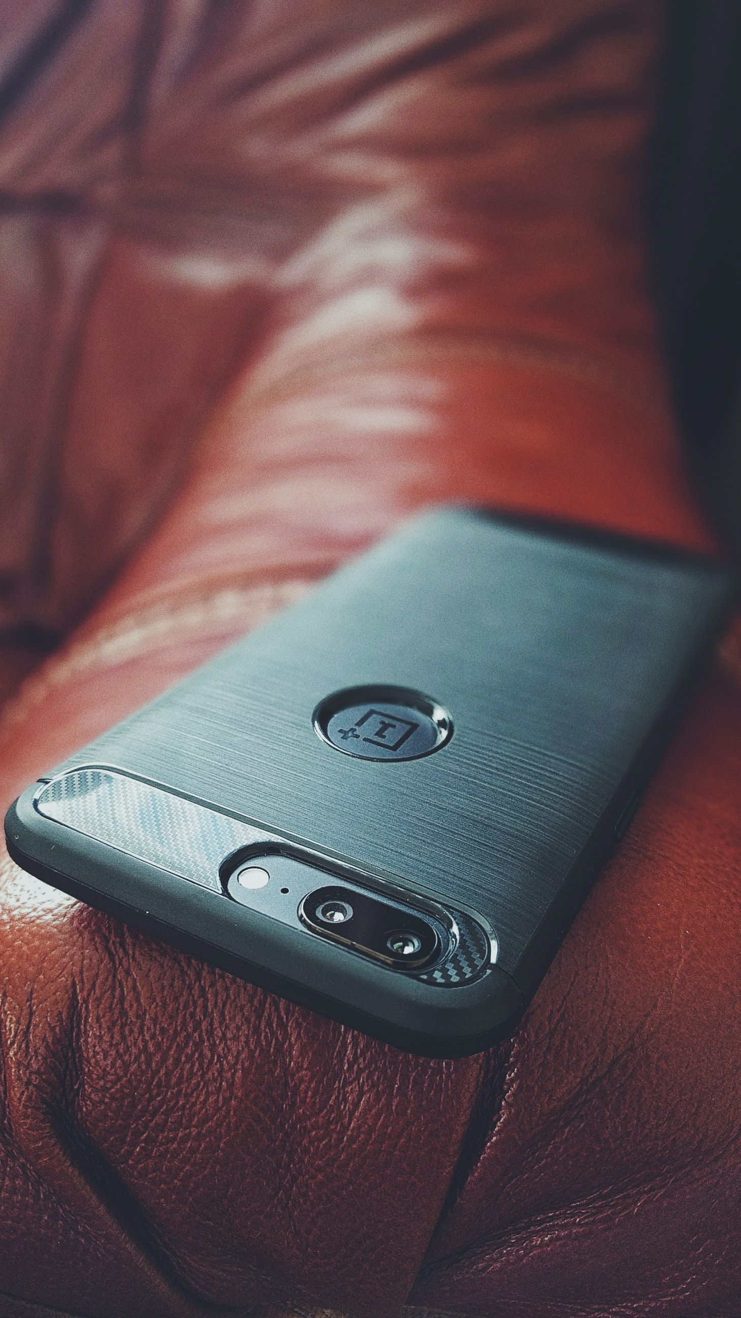 A smartphone sitting on the arm of a leather couch.