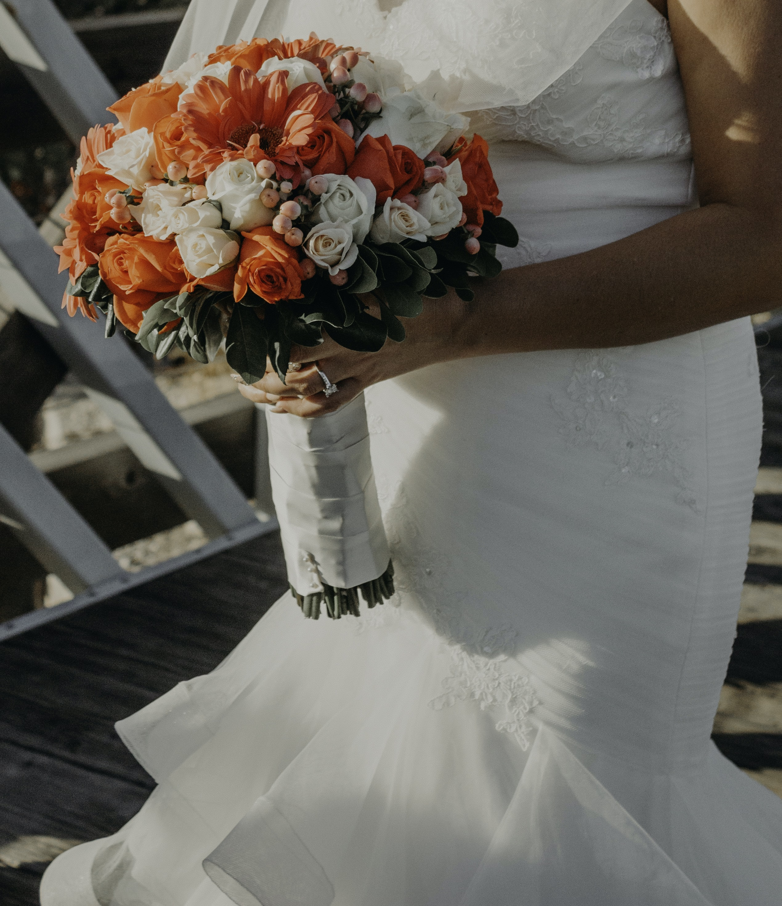 woman wearing white wedding gown holding red and white flower bouquet