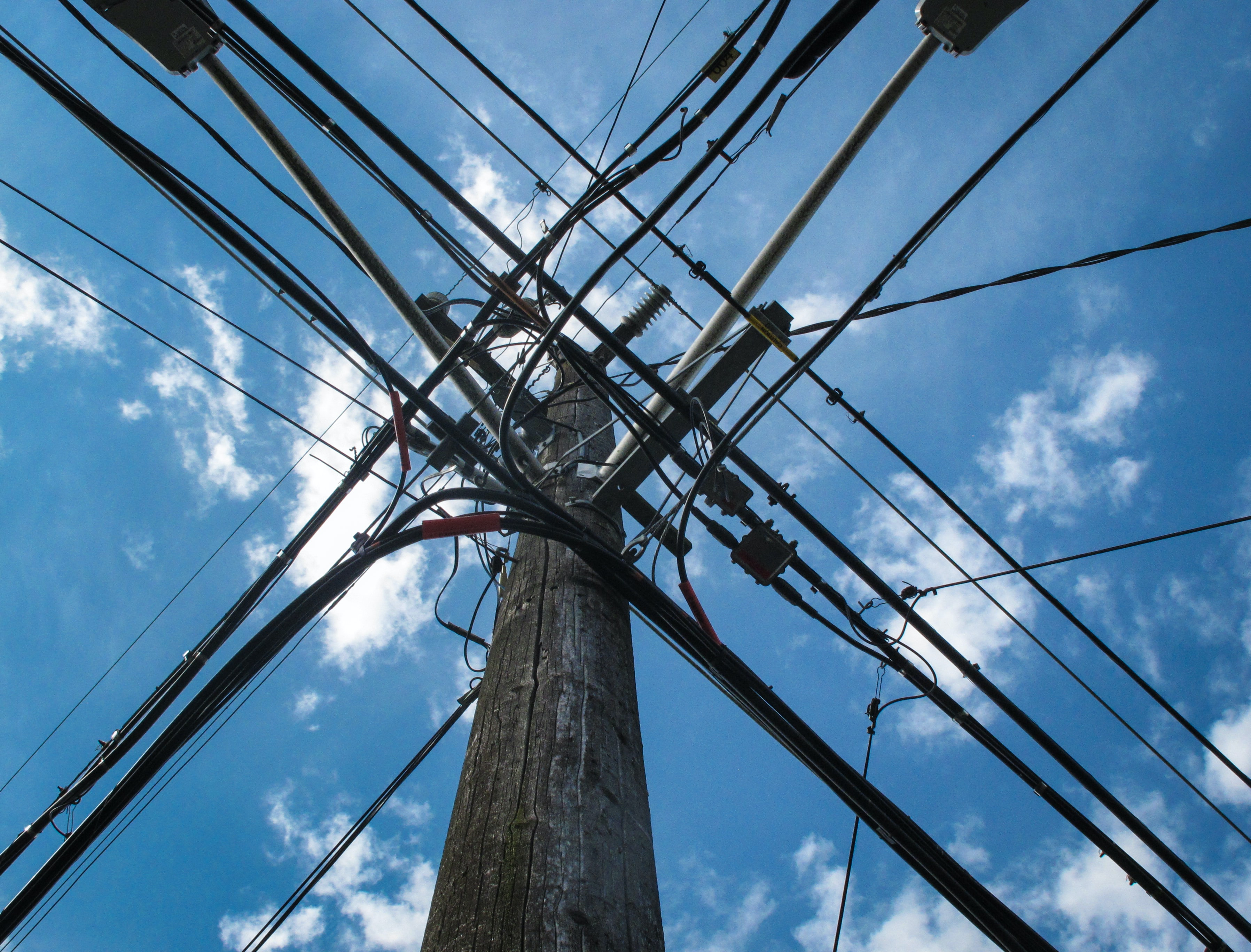 Industrial power lines and electrical wires form a grid against a blue sky